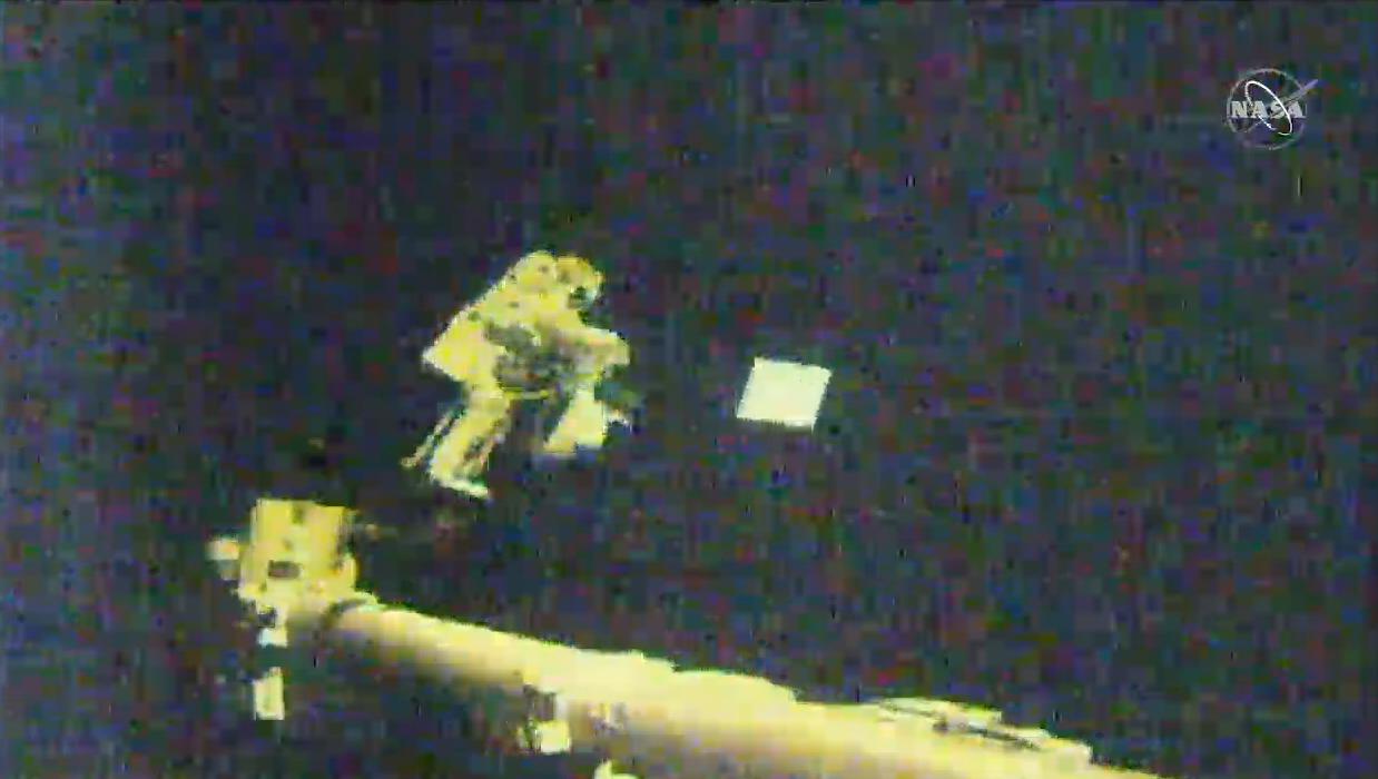 L'astronaute Victor Glover jette un couvercle d'antenne dans l'espace pour l'élimination tout en montant un bras robotique à l'extérieur de la Station spatiale internationale lors d'une sortie dans l'espace le 27 janvier 2021.