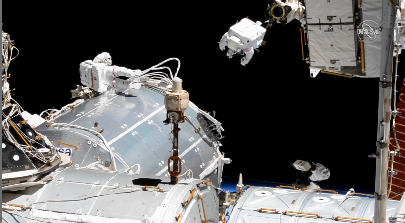 L'astronaute Victor Glover chevauche le bras robotique Canadarm2 à l'extérieur de la Station spatiale internationale tandis que son coéquipier Michael Hopkins de la NASA travaille à proximité lors d'une sortie dans l'espace le 27 janvier 2021.