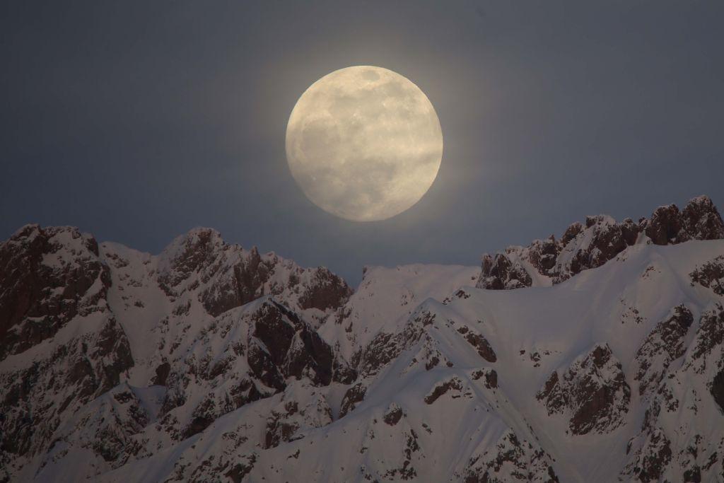 La pleine lune de neige se lève derrière les montagnes couvertes de neige dans la province de Hakkari en Turquie, le 20 janvier 2019.