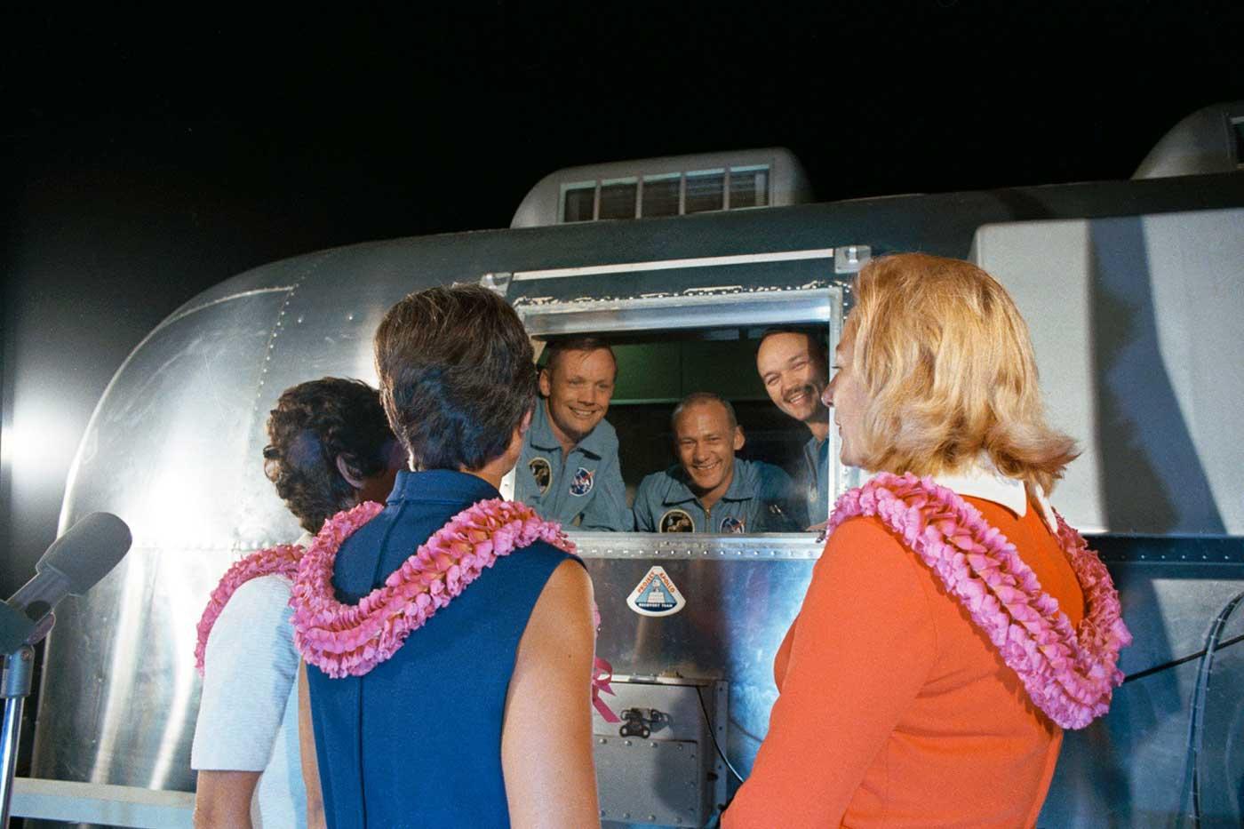 Après être rentré de la lune, l'équipage d'Apollo 11 est accueilli par leurs femmes alors qu'ils sont dans l'installation de quarantaine mobile.