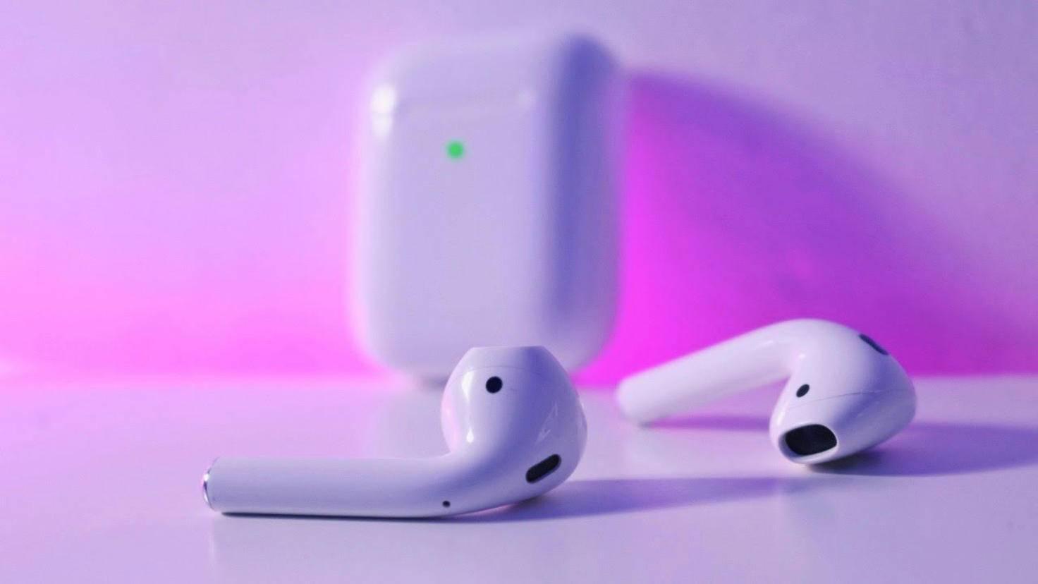 Les Apple AirPods 2 reposent sur une surface, tandis que le nouveau boîtier de chargement sans fil peut être vu en arrière-plan.