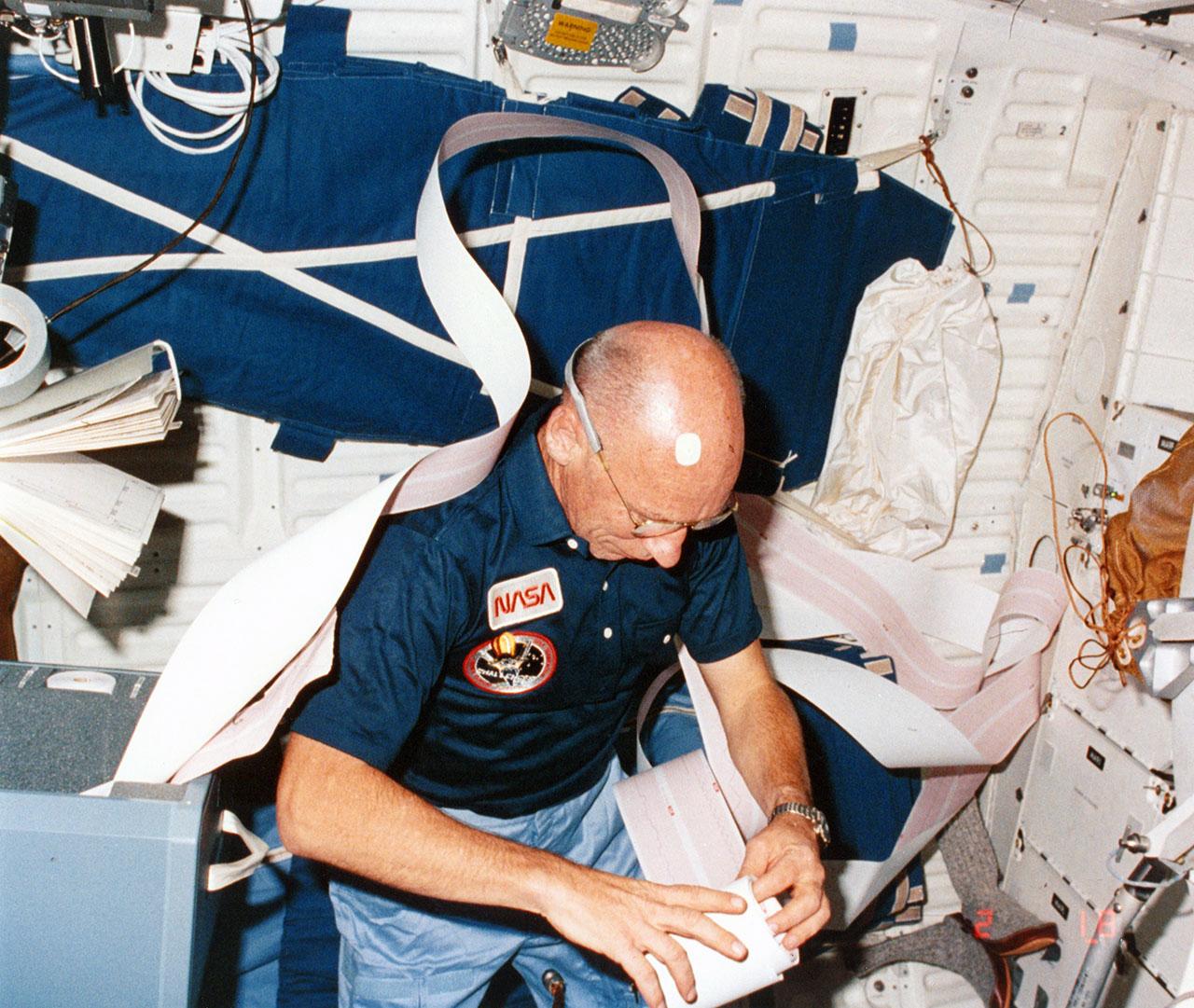 Bill Thornton, spécialiste de la mission STS-8, travaille avec un rouleau de papier télétype à bord de la navette spatiale Challenger en 1983.