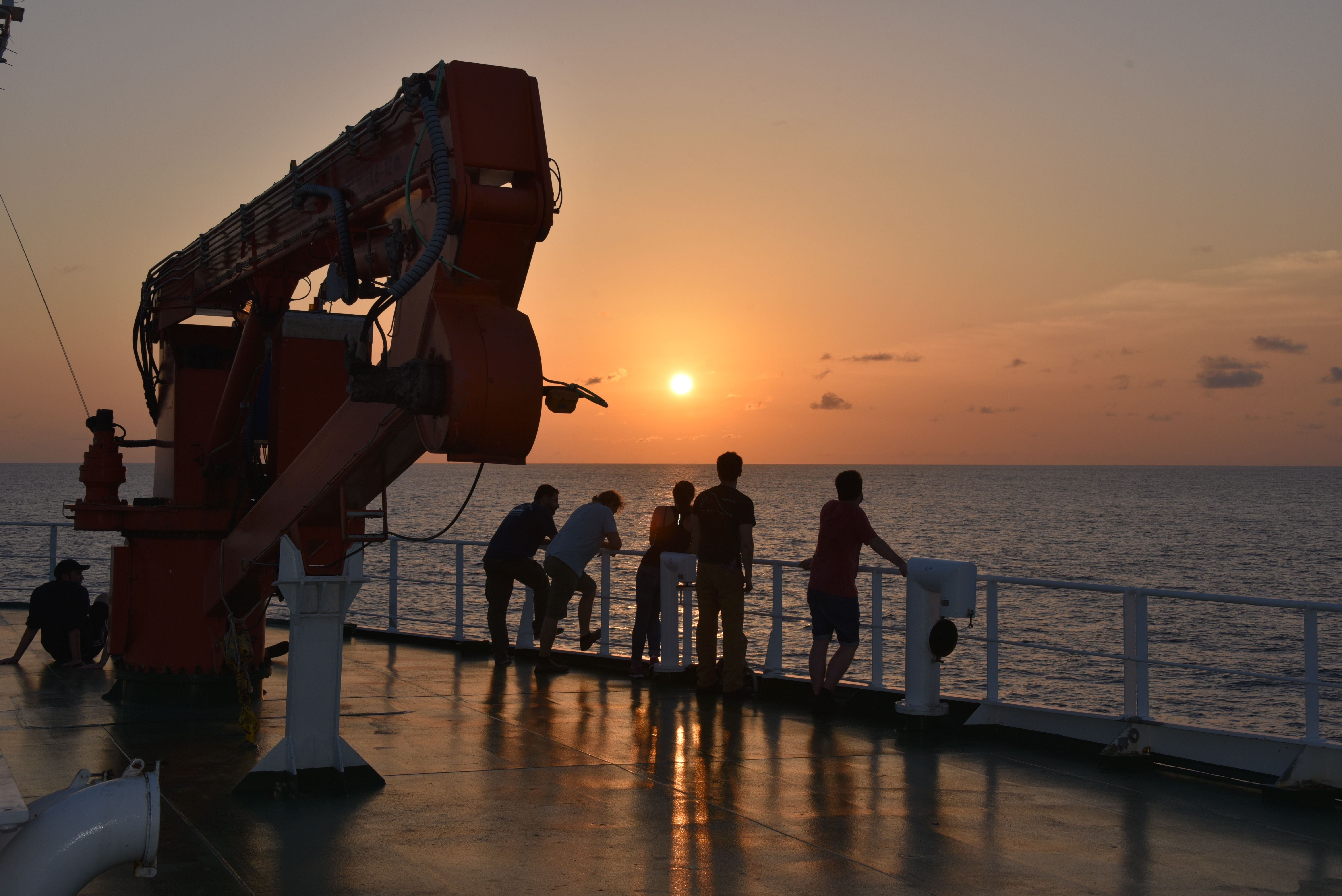L'équipage du navire de recherche regardant un coucher de soleil sur l'océan.