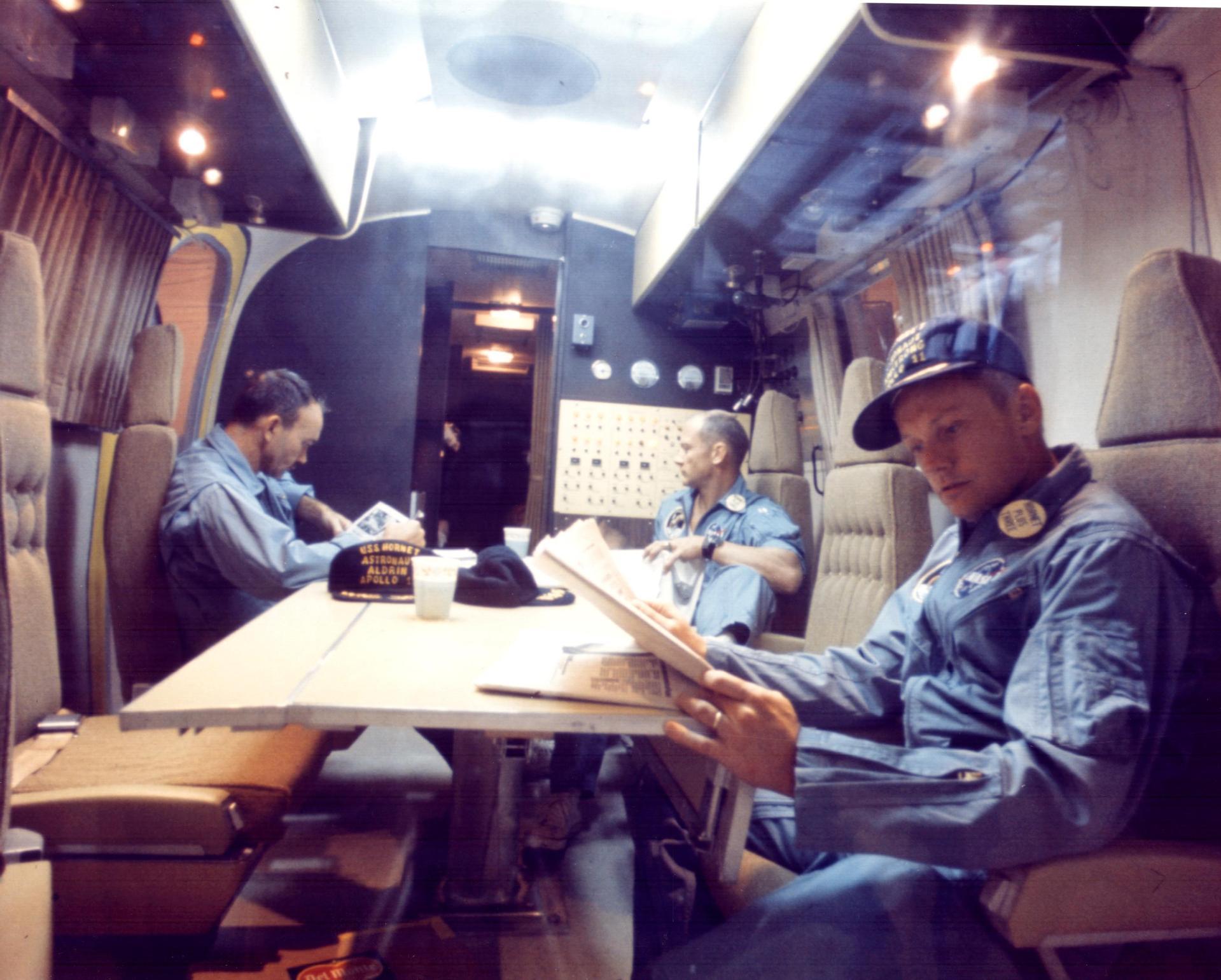 Michael Collins, Buzz Aldrin et Neil Armstrong vus à l'intérieur de l'installation de quarantaine mobile lors du voyage de retour de 2,5 jours au port sur l'USS Hornet, qui les a récupérés lorsqu'ils ont éclaboussé.