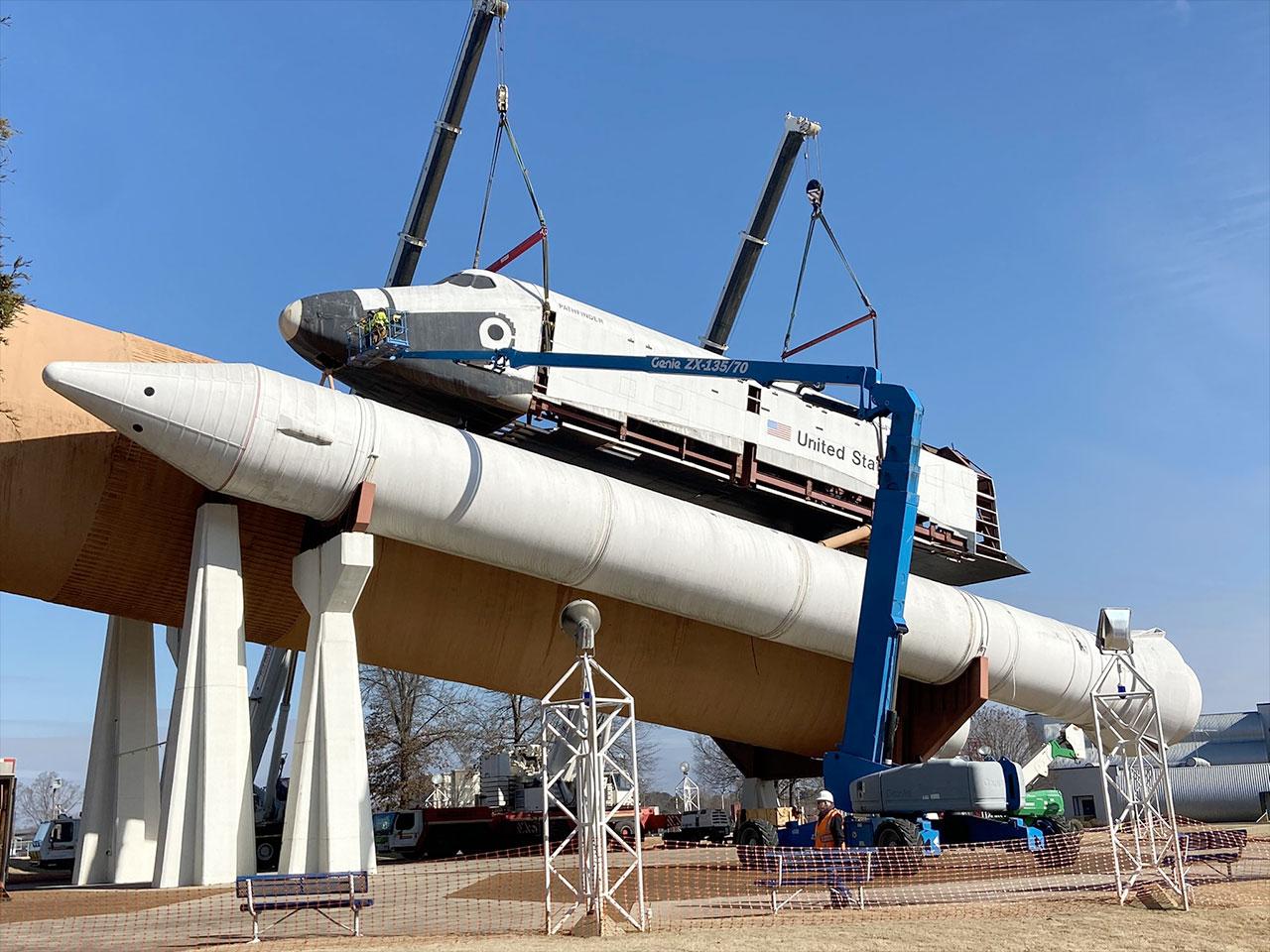 De grandes grues ont été utilisées pour abaisser l'orbiteur de la navette spatiale partiellement démonté.