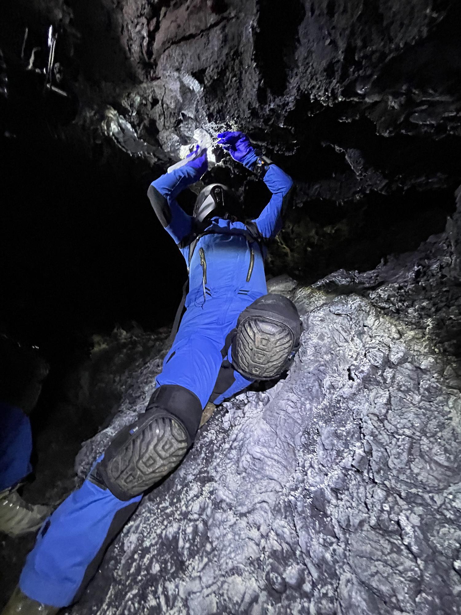 Cmdr.  Michaela Musilova recueille des échantillons extrémophiles dans une grotte de lave pour la recherche en astrobiologie.
