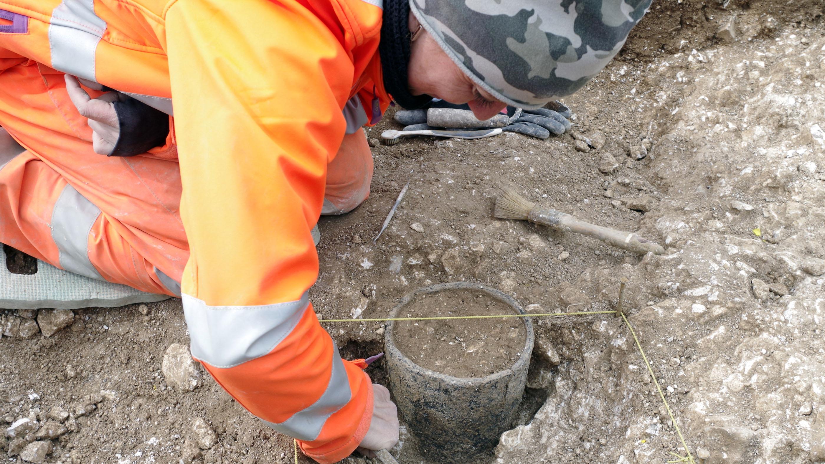 Un archéologue de Wessex Archaeology fouille un pot de l'âge du bronze découvert lors des travaux préliminaires sur le site du tunnel proposé près de Stonehenge.