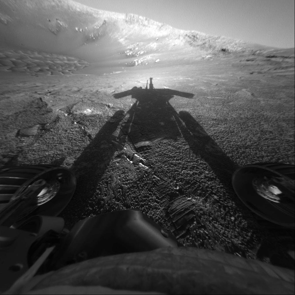 Le rover Opportunity de la NASA sur Mars regarde loin du soleil dans le cratère Endurance et voit son ombre.  L'image a été prise vers l'est peu avant le coucher du soleil le 3609e jour martien, ou sol, du travail d'Opportunity sur Mars (20 mars 2014).