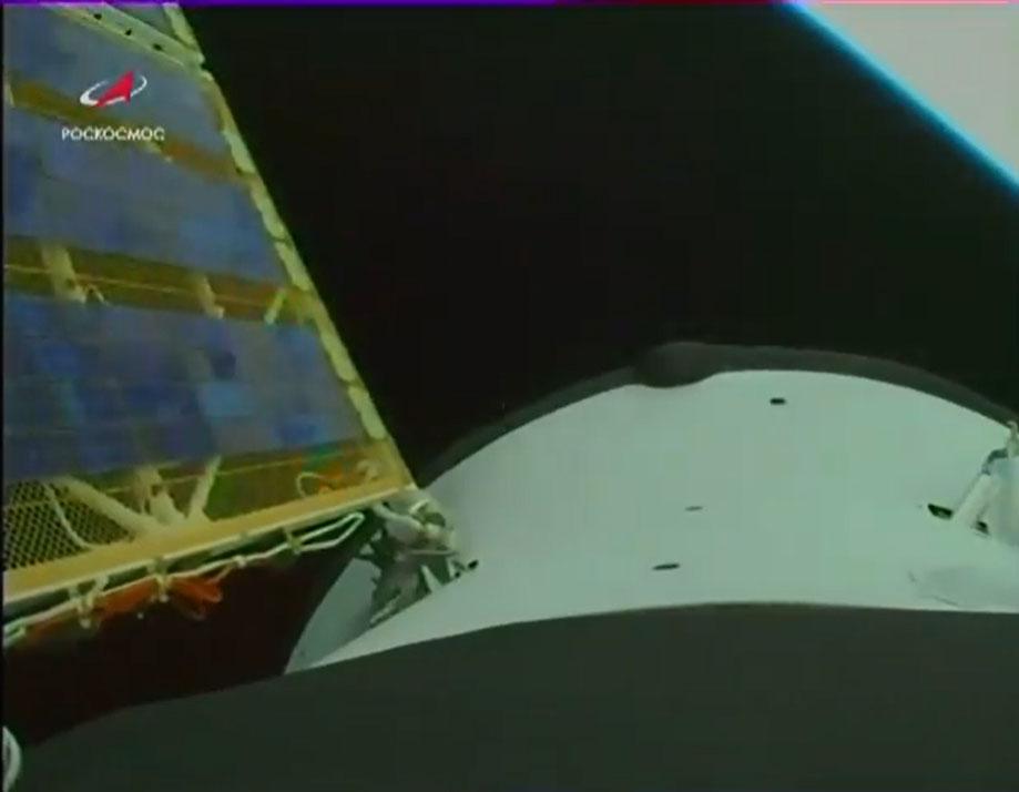 Un éclat de la Terre peut être vu en haut à droite dans cette vue de la caméra de Progress 77 capturée peu de temps après le lancement.  Un si ses panneaux solaires sont visibles à gauche après le déploiement.