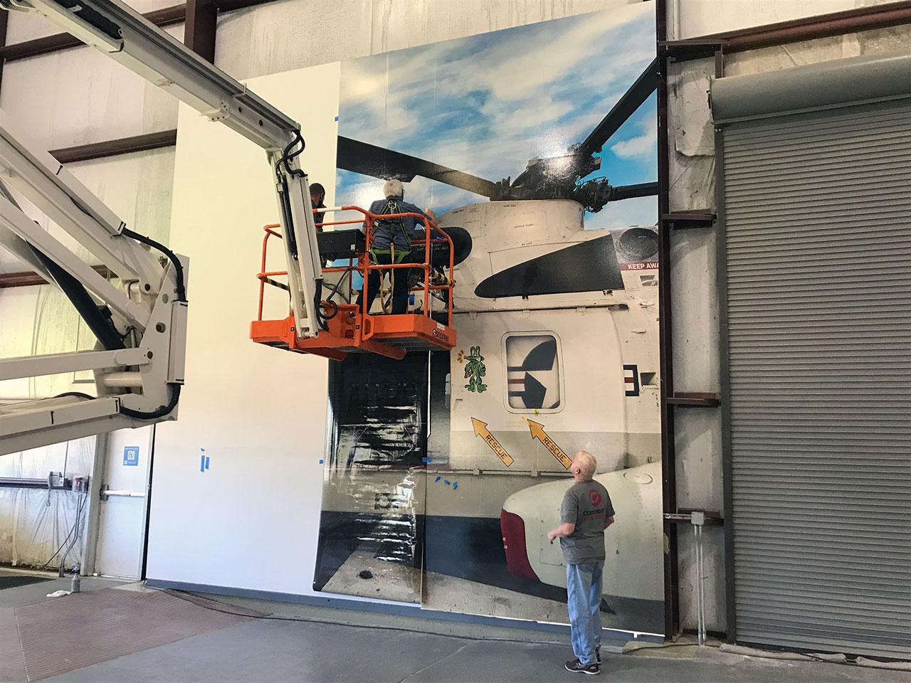 Une peinture murale photo-réaliste de Helo 66, un hélicoptère Sikorsky Sea King utilisé pour récupérer les équipages d'Apollo après leurs éclaboussures, sert de toile de fond à la statue d'Apollo 13 à l'intérieur du bâtiment Saturn V au Space Center Houston.