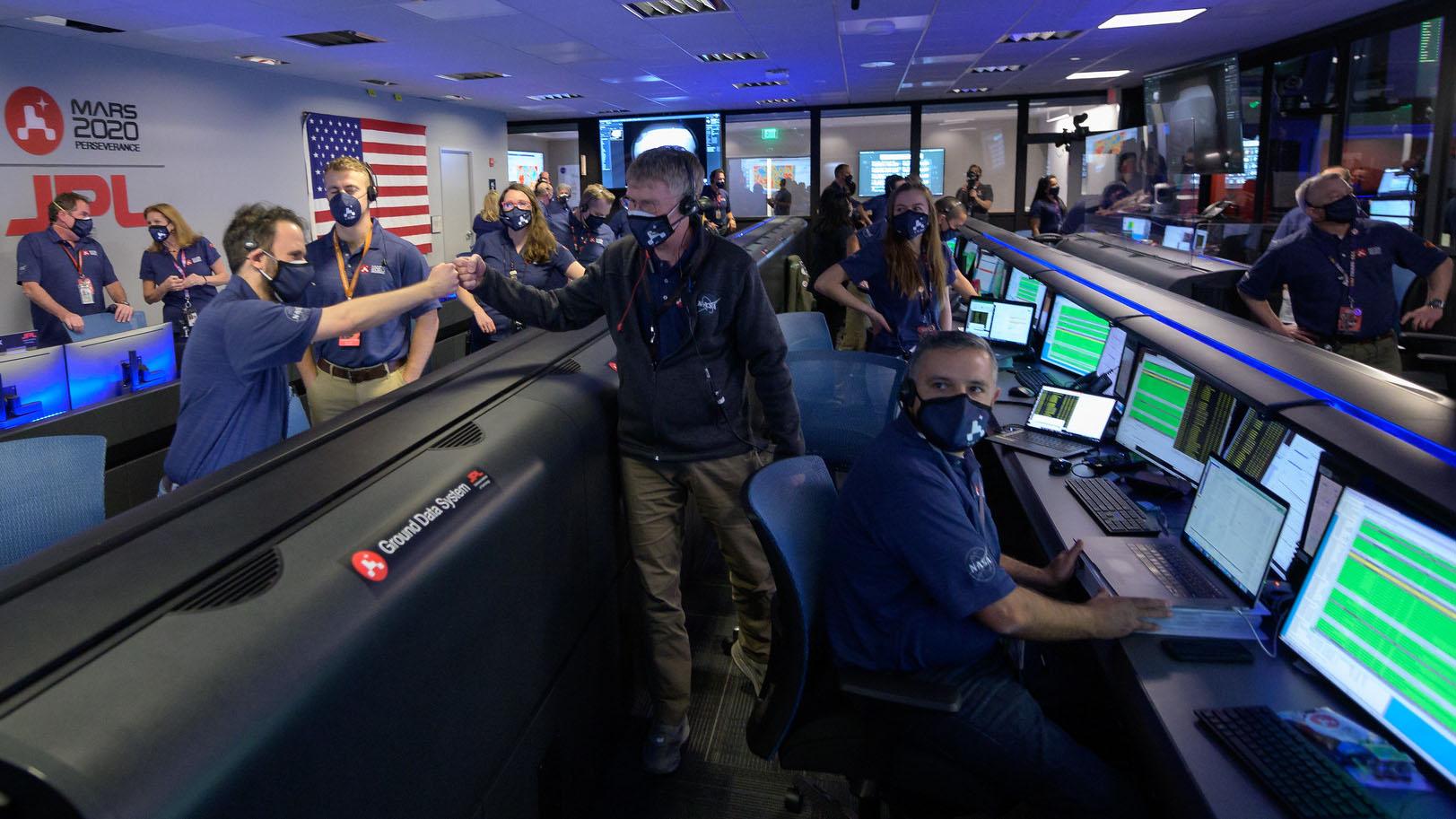 Les membres de l'équipe de rover Perseverance de la NASA réagissent au contrôle de mission après avoir reçu la confirmation que le vaisseau spatial a atterri avec succès sur Mars, le jeudi 18 février 2021, au Jet Propulsion Laboratory de la NASA à Pasadena, en Californie.