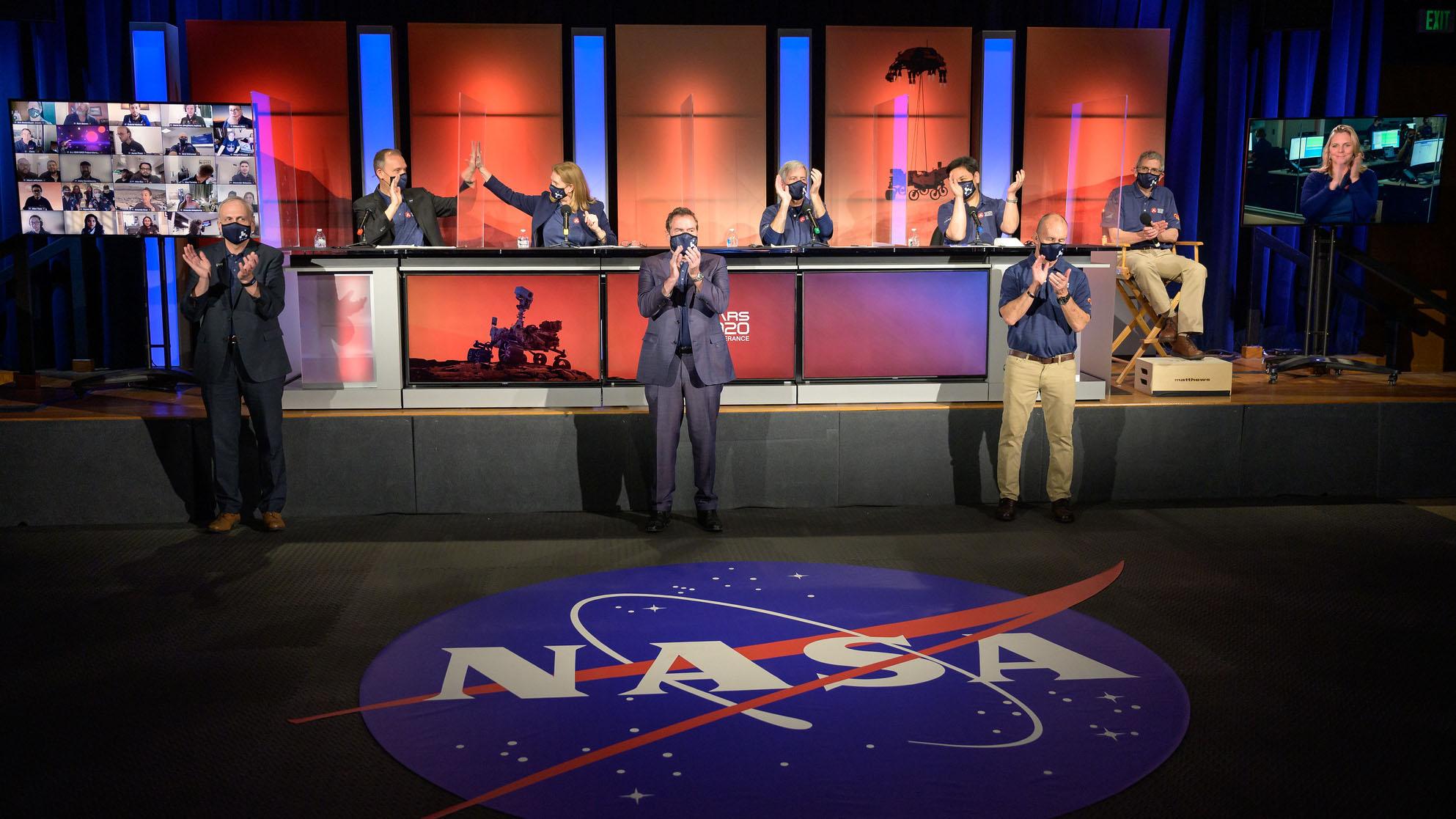 La direction de la mission du rover Perseverance de la NASA et un scientifique célèbrent un atterrissage réussi sur Mars au début d'une mise à jour post-atterrissage, le jeudi 18 février 2021, au Jet Propulsion Laboratory de la NASA à Pasadena, en Californie.