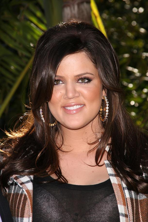 khloe kardashian veste à carreaux souriante avec boucles d'oreilles et bosse de cheveux