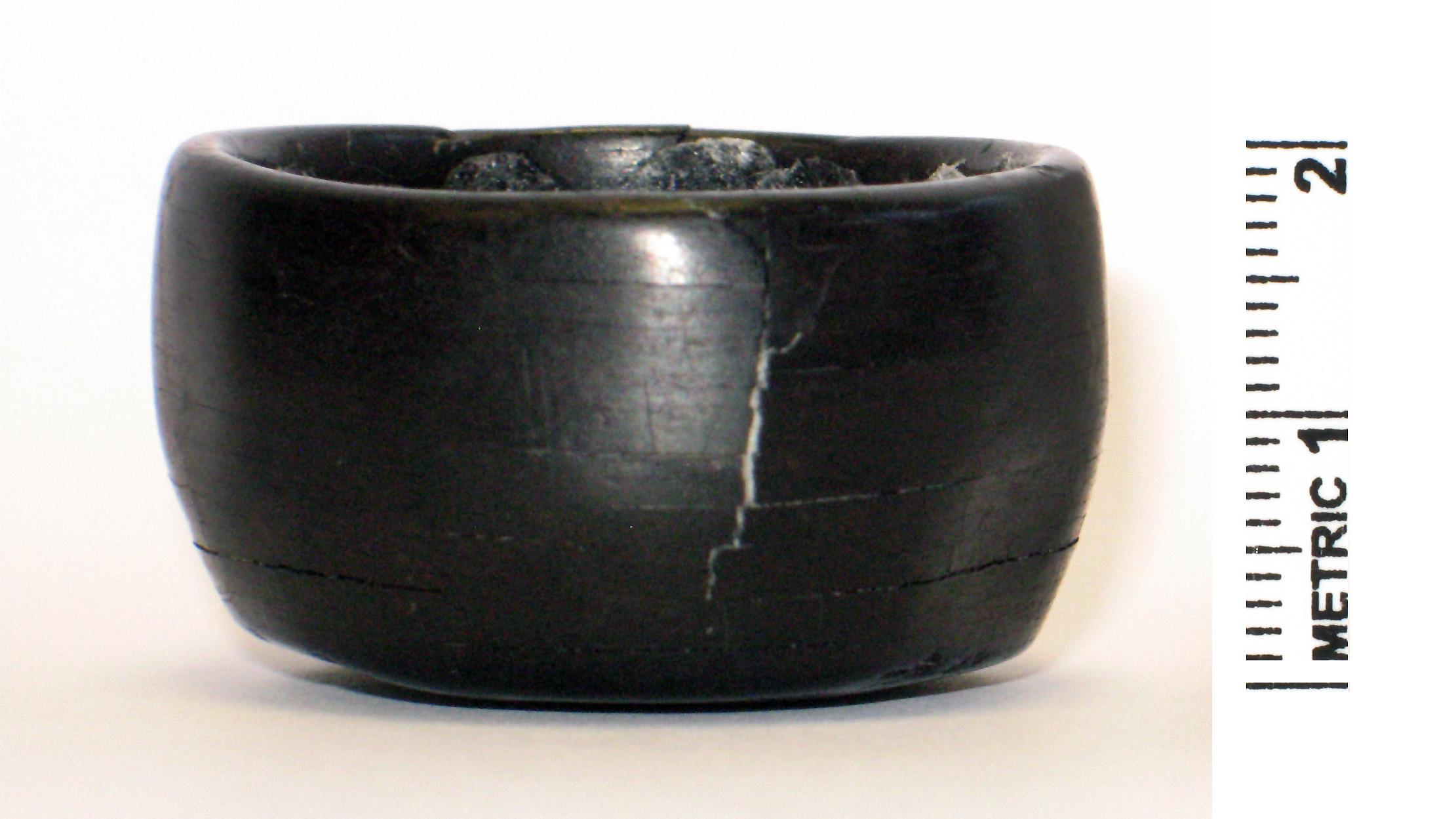 Cet étrange objet cylindrique, fait de schiste, a été découvert dans l'une des anciennes tombes.  Il peut avoir fait partie d'un personnel de cérémonie ou d'un club.