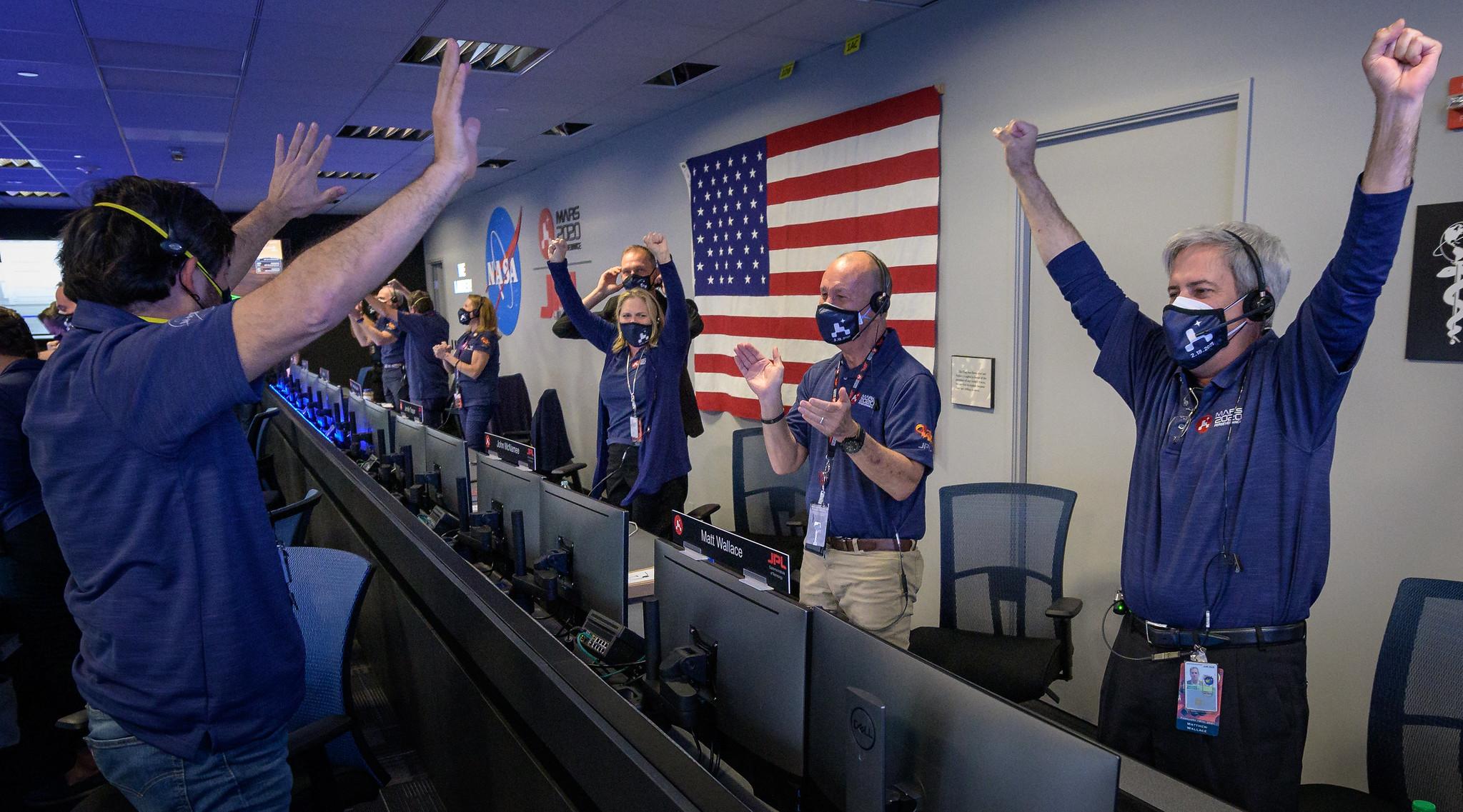 Les membres de l'équipe de rover Perseverance de la NASA réagissent au contrôle de mission après avoir reçu la confirmation que le vaisseau spatial a atterri avec succès sur Mars, le jeudi 18 février 2021, au Jet Propulsion Laboratory de la NASA à Pasadena, en Californie.  L'équipe est masquée et éloignée conformément aux précautions de sécurité COVID-19.