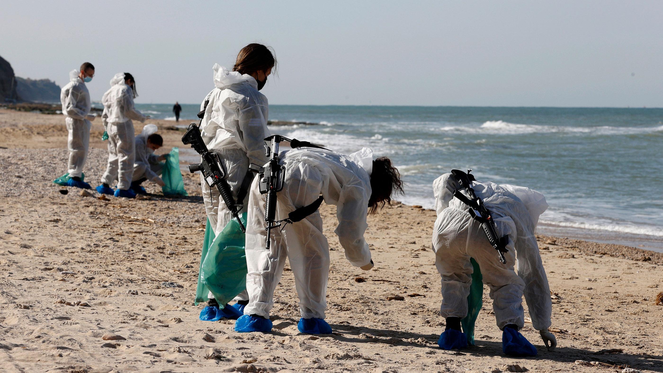 Des soldats israéliens enlèvent des boules de goudron lors de l'opération de nettoyage au parc national de Sharon Beach le 22 février.