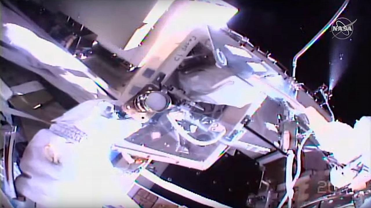 Dans une vue de la caméra du casque de l'astronaute de la NASA Michael Hopkins, on peut voir du liquide de refroidissement à l'ammoniac se répandre dans l'espace (à droite) dans le cadre des tâches de Hopkins et Victor Glover lors d'une sortie dans l'espace le samedi 13 mars 2021 à l'extérieur de la Station spatiale internationale.