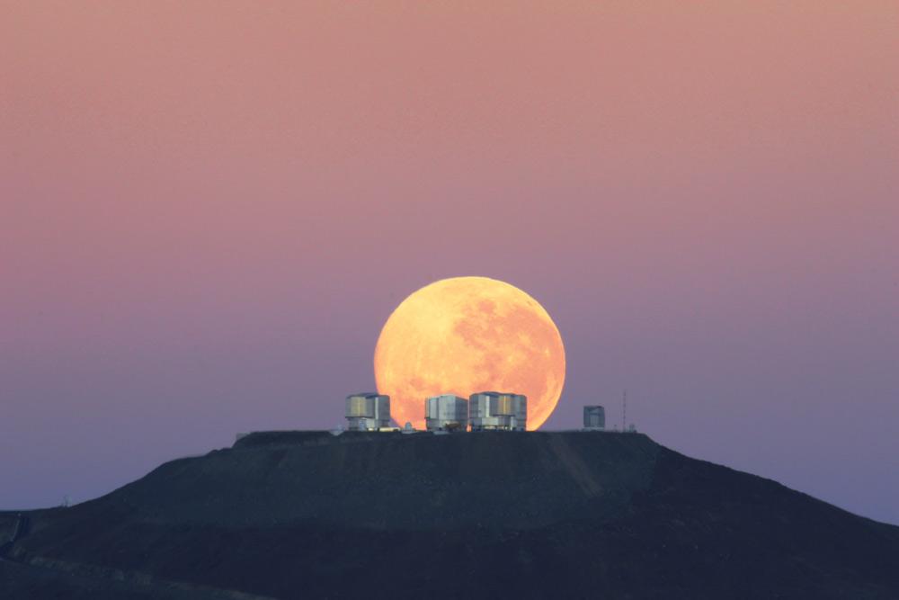 La pleine lune semble massive alors qu'elle se couche derrière le très grand télescope dans le désert d'Atacama au Chili, dans cette photo du 7 juin 2010. Pourquoi les observateurs rapportent-ils que la lune semble plus grande près de l'horizon qu'elle ne le fait haut dans le ciel?  Ce n'est peut-être rien de plus qu'un truc de perspective.