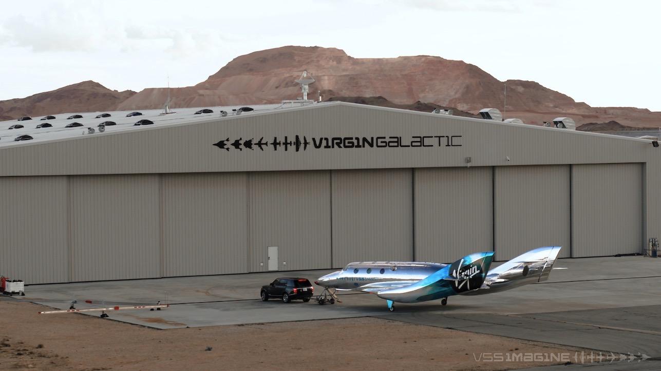 VSS Imagine et un véhicule de remorquage devant le hangar de Virgin Galactic à Spaceport America au Nouveau-Mexique.