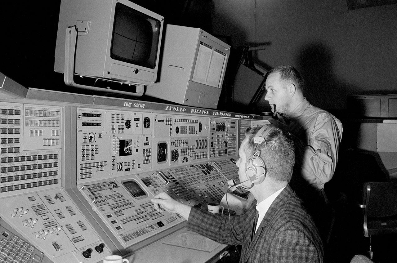 L'astronaute de la NASA Philip Chapman, debout avec un tuyau, suit une formation dans le simulateur de module de commande Apollo en 1968.