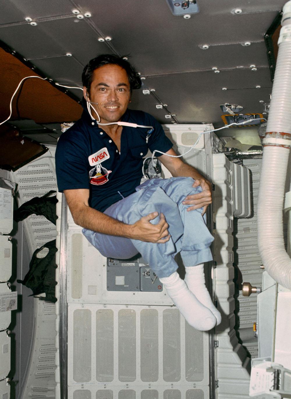 L'astronaute Robert L.Crippen, pilote de STS-1 profite de l'apesanteur pour faire de rares acrobaties sur le pont intermédiaire de la navette spatiale Columbia en orbite terrestre lors de la mission de deux jours entre le 12 avril et le 14 avril 1981.