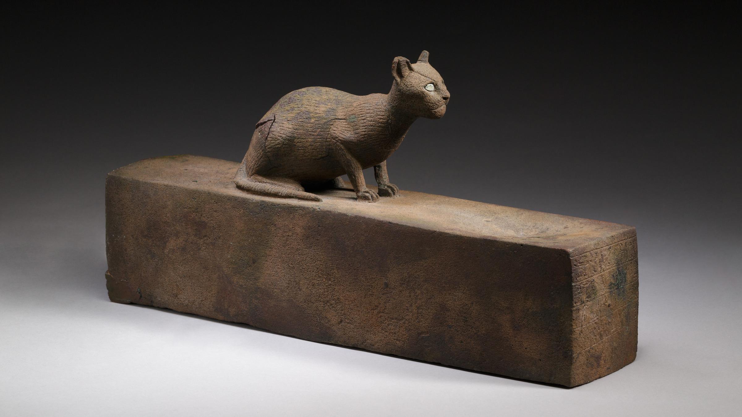 Un chat, probablement une représentation de la déesse Bastet, au sommet d'une boîte pour une momie animale.  Il date de la période tardive – période ptolémaïque (664–30 av. J.-C.).