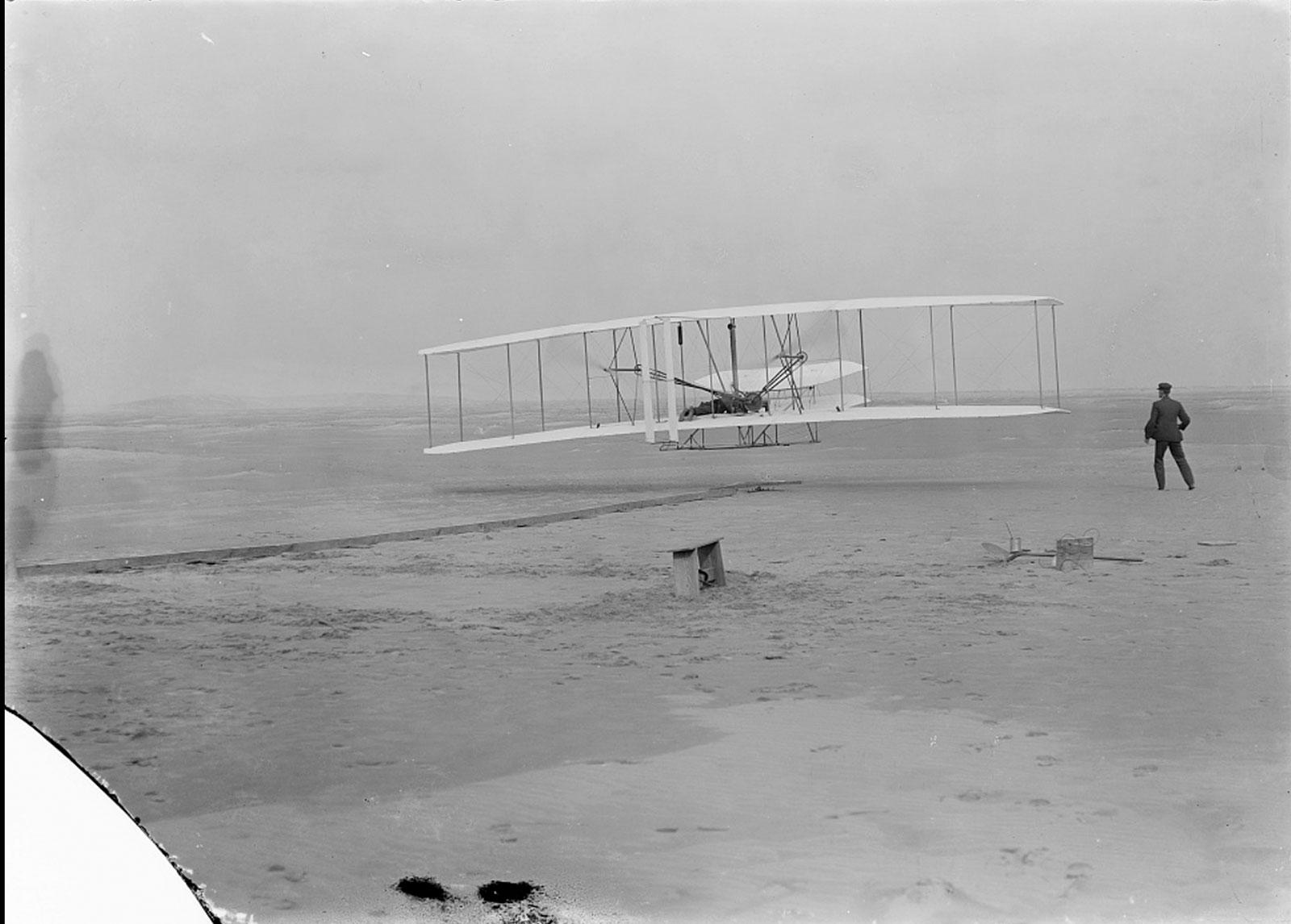 Le Flyer 1, contrôlé par Orville Wright, effectue le premier vol motorisé de l'histoire à Kitty Hawk, en Caroline du Nord, le 17 décembre 1903. Le frère d'Orville, Wilbur, regarde sur cette photo, qui a été prise par John Daniels, membre de l'US Life- Station d'épargne à Kill Devil Hills, Caroline du Nord.