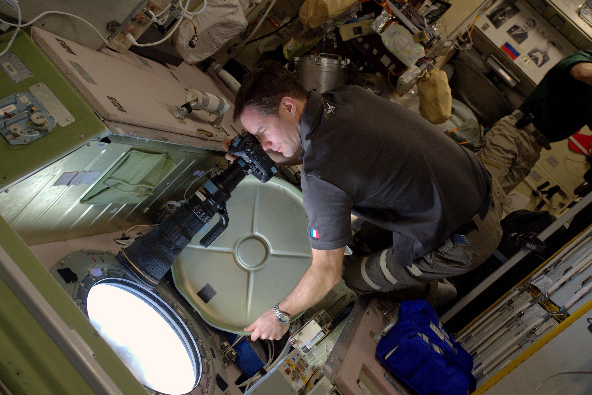 L'astronaute de l'Agence spatiale européenne Thomas Pesquet prend des photos à travers une fenêtre de la Station spatiale internationale.