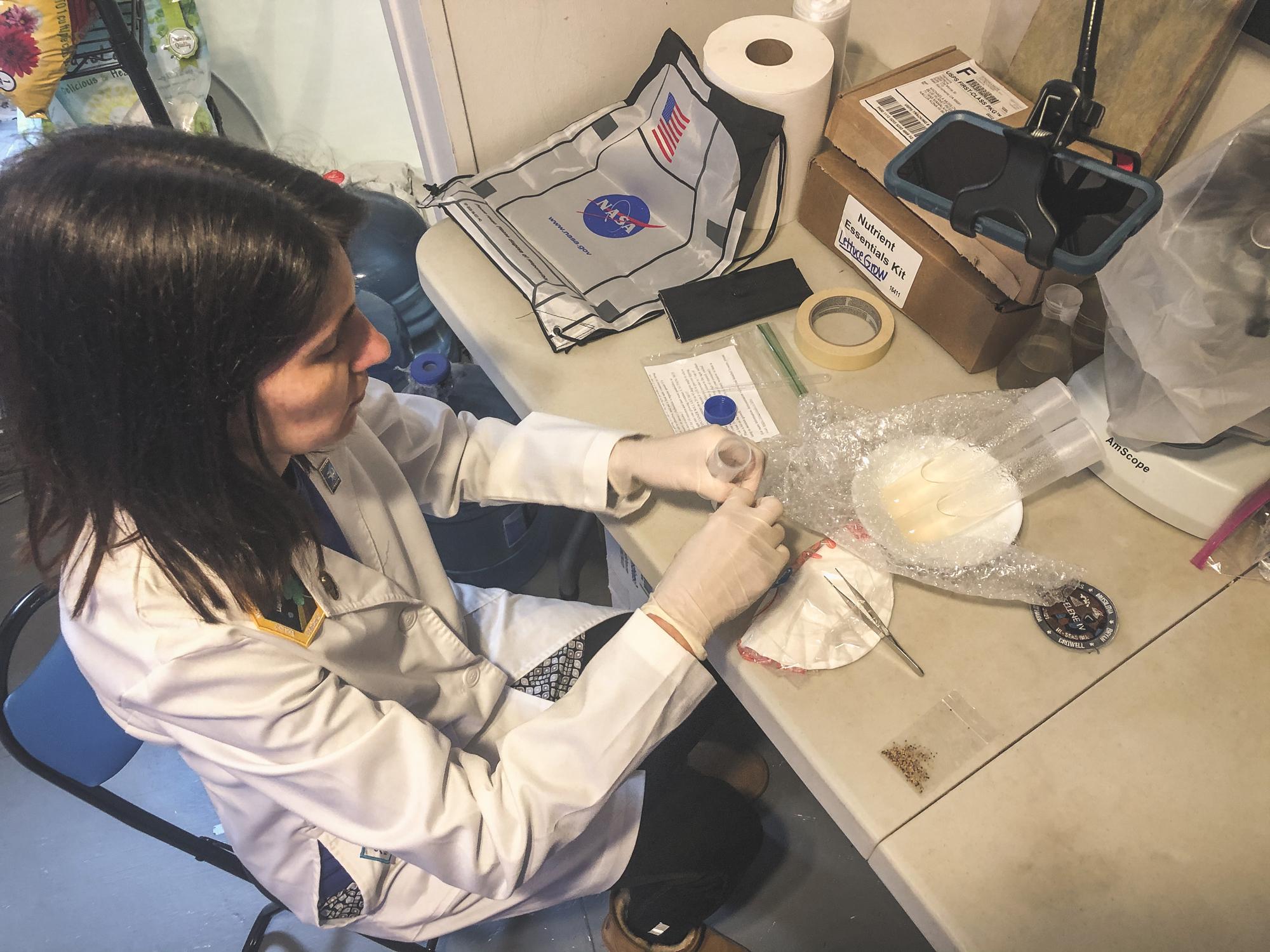 L'officier des opérations Lori Waters prépare son expérience de croissance hydroponique de trèfle ExoLab.