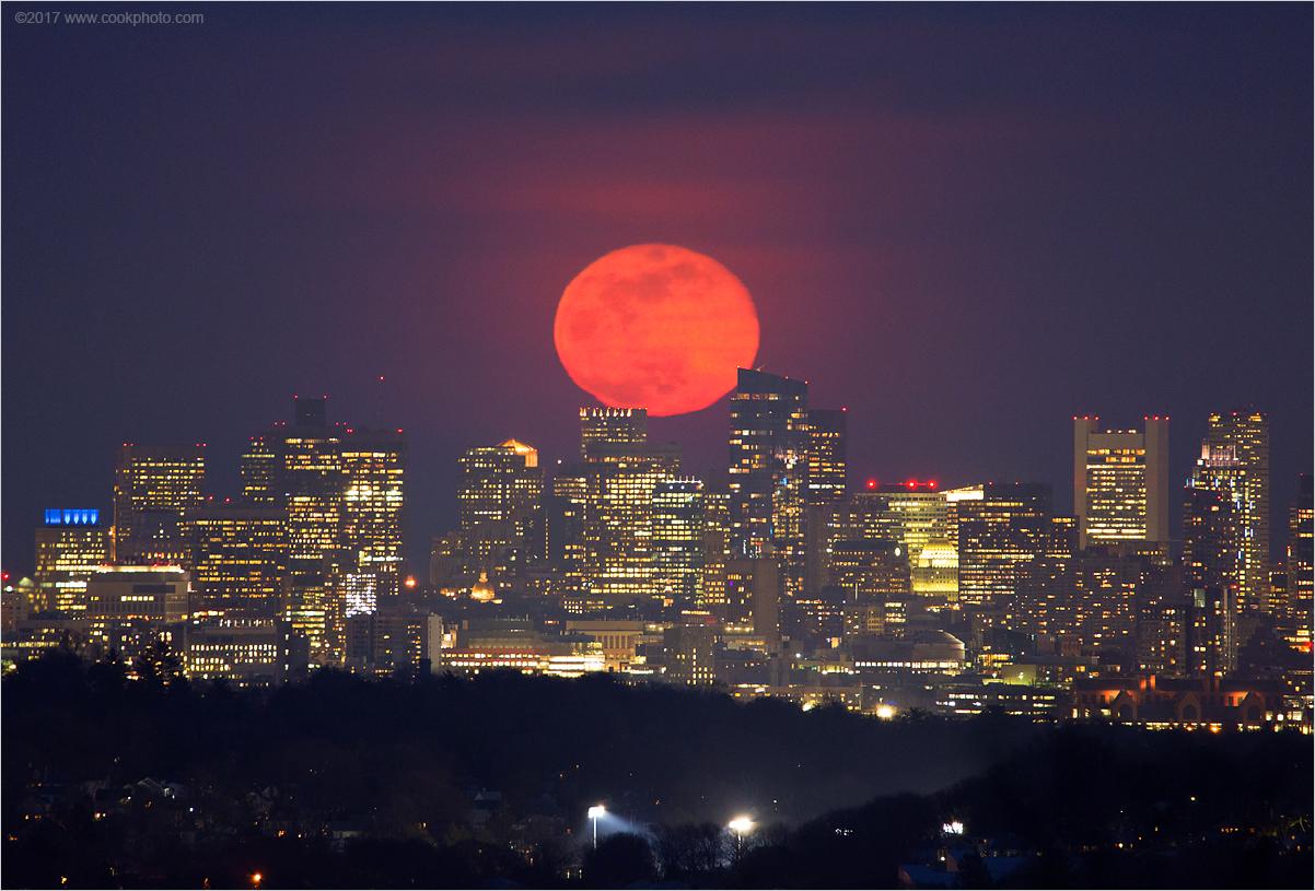 La pleine lune rose se lève au-dessus de Boston sur cette photo prise par Chris Cook mercredi 11 avril.  La pleine lune d'avril n'est pas vraiment rose;  il porte le nom du phlox terrestre sauvage, l'une des premières fleurs à fleurir au printemps.  Cook a déclaré que la pleine lune était rouge-orange ce soir-là en raison de l'atmosphère épaisse, de la poussière, de la brume et du pollen dans l'air.