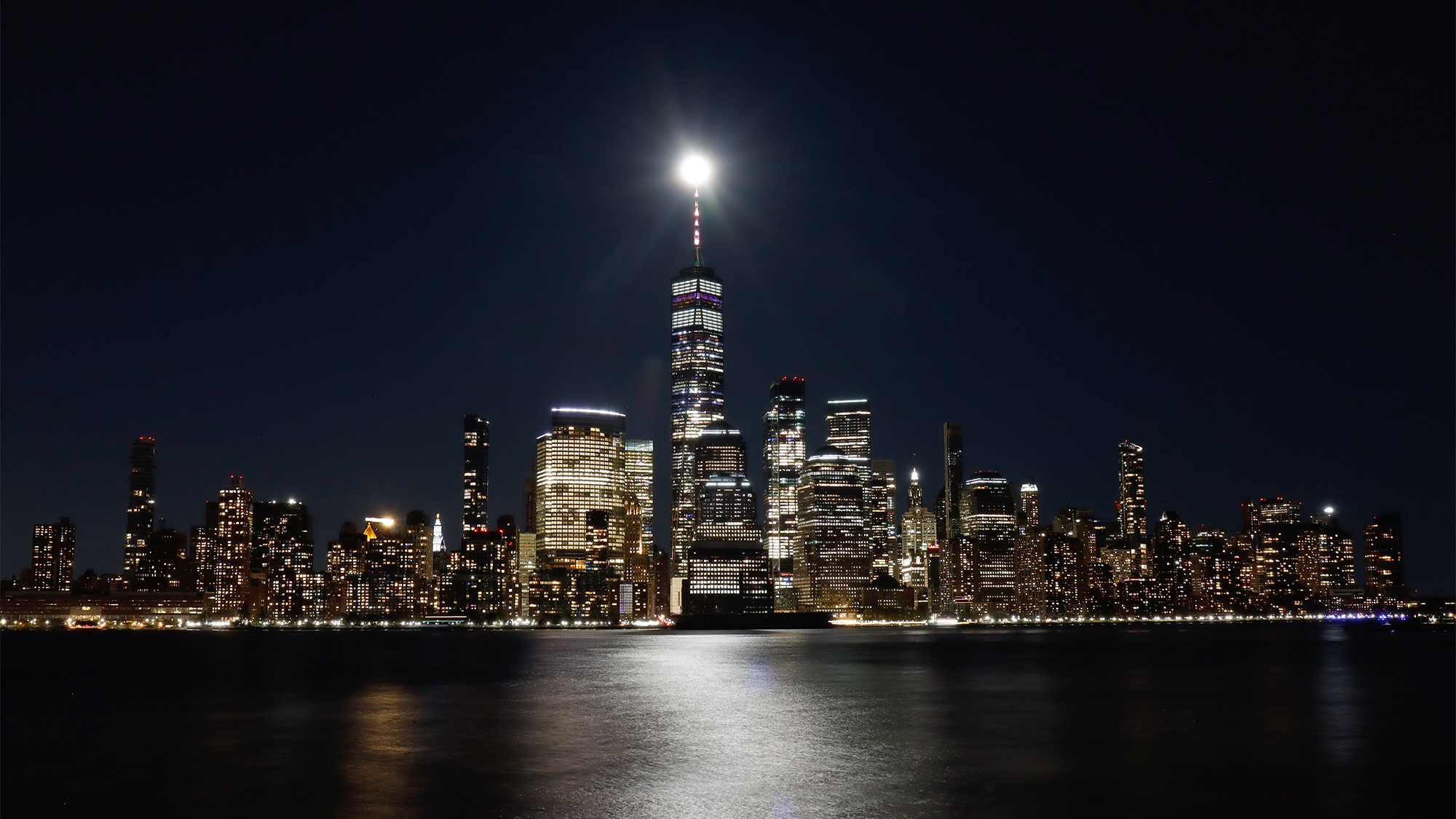 Vues de la Super Pink Moon au-dessus de Manhattan et du One World Trade Center à New York le 26 avril 2021, depuis Jersey City, New Jersey.