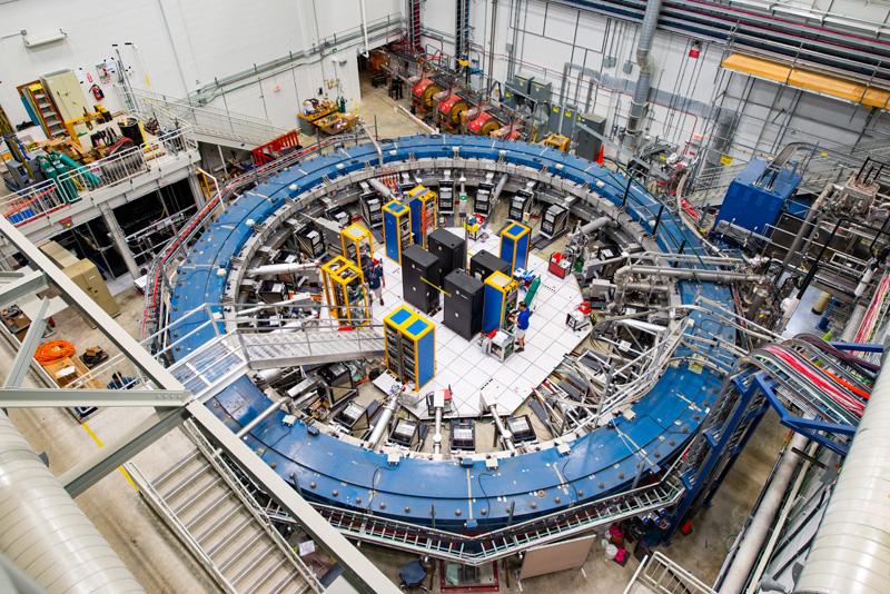 Une vue de dessus de l'équipement utilisé dans l'expérience g-2 au Laboratoire Fermi.  L'expérience utilise une ligne de faisceau de muons, des racks électroniques et un anneau de stockage magnétique supraconducteur refroidi à moins 450 degrés Fahrenheit (moins 267 degrés Celsius) pour étudier l'oscillation des muons.
