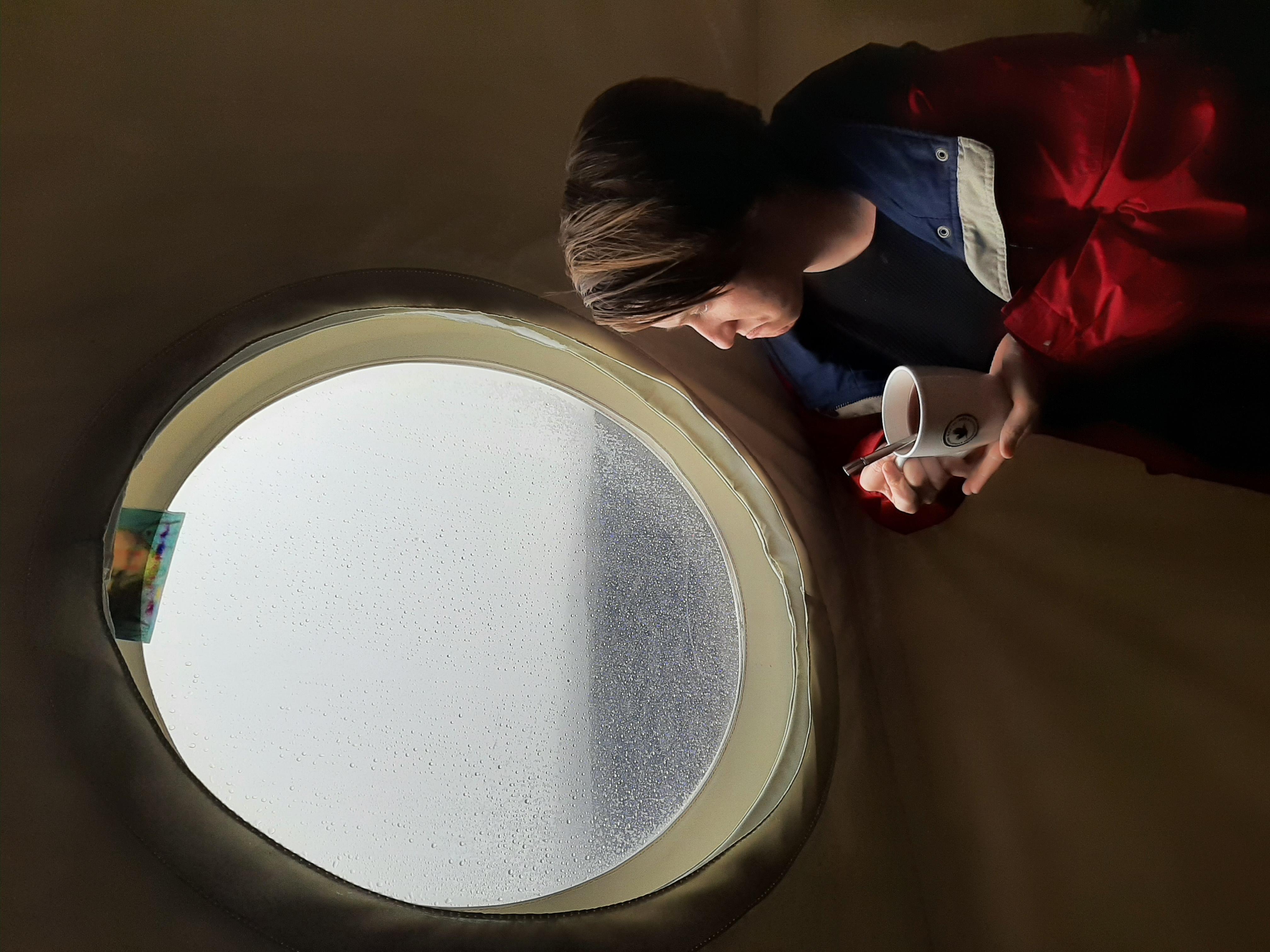 Crew Bioengineer Zoe Maxwell regarde tristement l'une des deux fenêtres de HI-SEAS, car la vue est celle de nuages gris depuis plus d'une semaine.