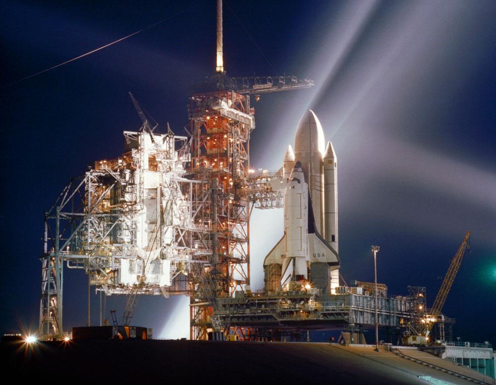 La navette spatiale Columbia, premier orbiteur de la NASA, est éclairée dans cette scène nocturne à Launch Pad 39A au Kennedy Space Center à Cap Canaveral, en Floride, pendant les préparatifs du premier vol (STS-1) du nouveau système de vaisseau spatial réutilisable de la NASA