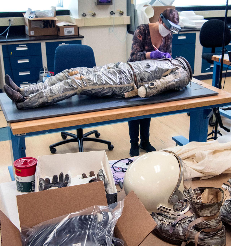 La combinaison de pression Mercury d'Alan Shepard est préparée pour sa prochaine exposition dans le laboratoire de conservation du Steven F.Udvar-Hazy Center du National Air and Space Museum à Chantilly, en Virginie.  Le casque, les gants et les bottes de Shepard sont visibles au premier plan.