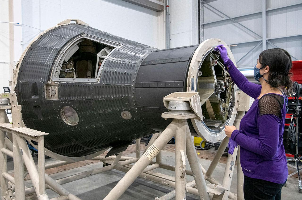 Un restaurateur du National Air and Space Museum travaille autour du compartiment de récupération de Freedom 7, la capsule Mercury d'Alan Shepard, dans le hangar de restauration Mary Baker Engen au Steven F.Udvar-Hazy Center à Chantilly, en Virginie.