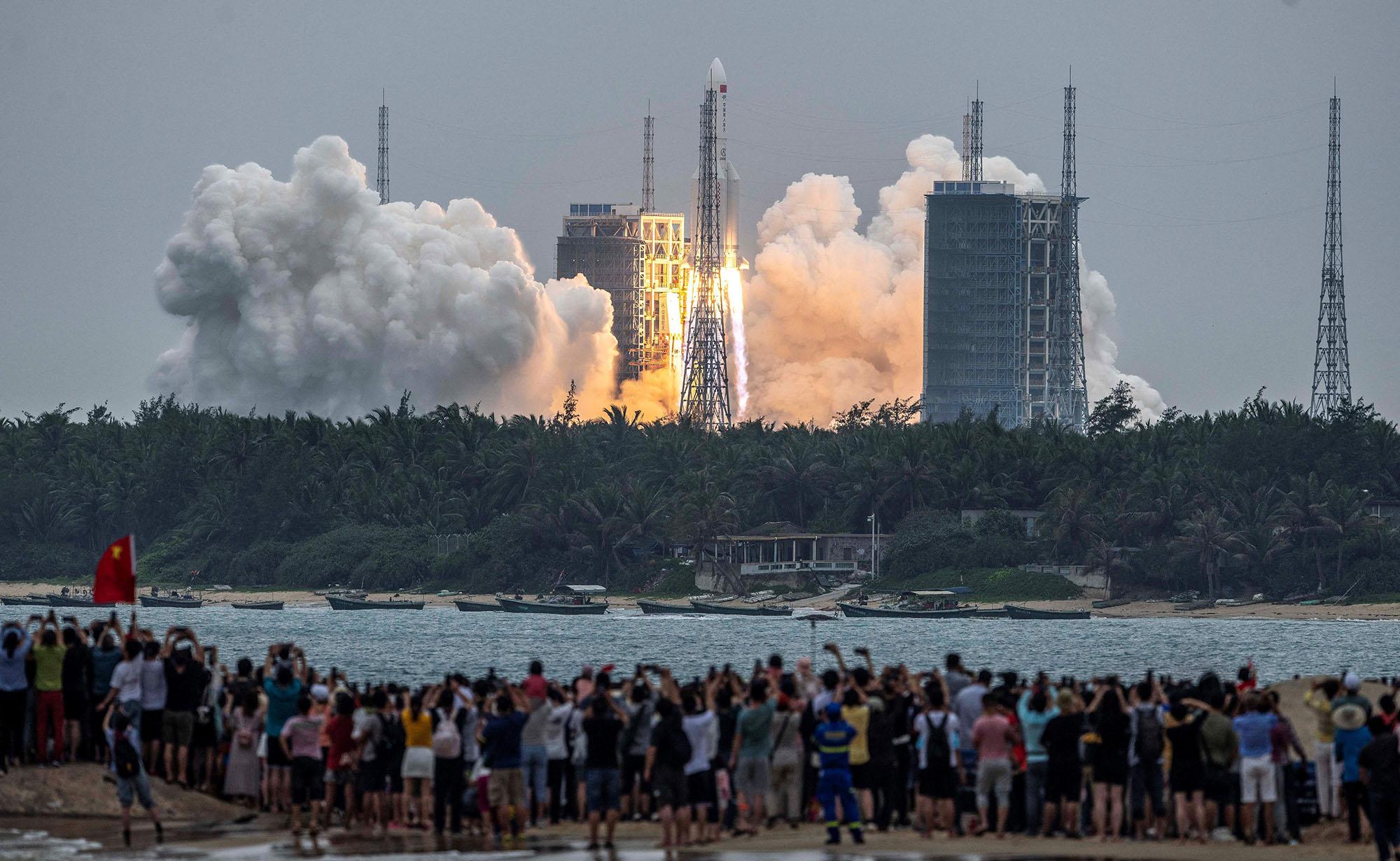 Les gens regardent une fusée Longue Marche 5B, transportant le module central de la station spatiale chinoise Tianhe, alors qu'elle décolle du centre de lancement spatial de Wenchang dans la province de Hainan, dans le sud de la Chine, le 29 avril 2021.