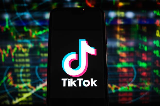 Un logo TikTok est affiché sur un smartphone avec des pourcentages boursiers en arrière-plan.