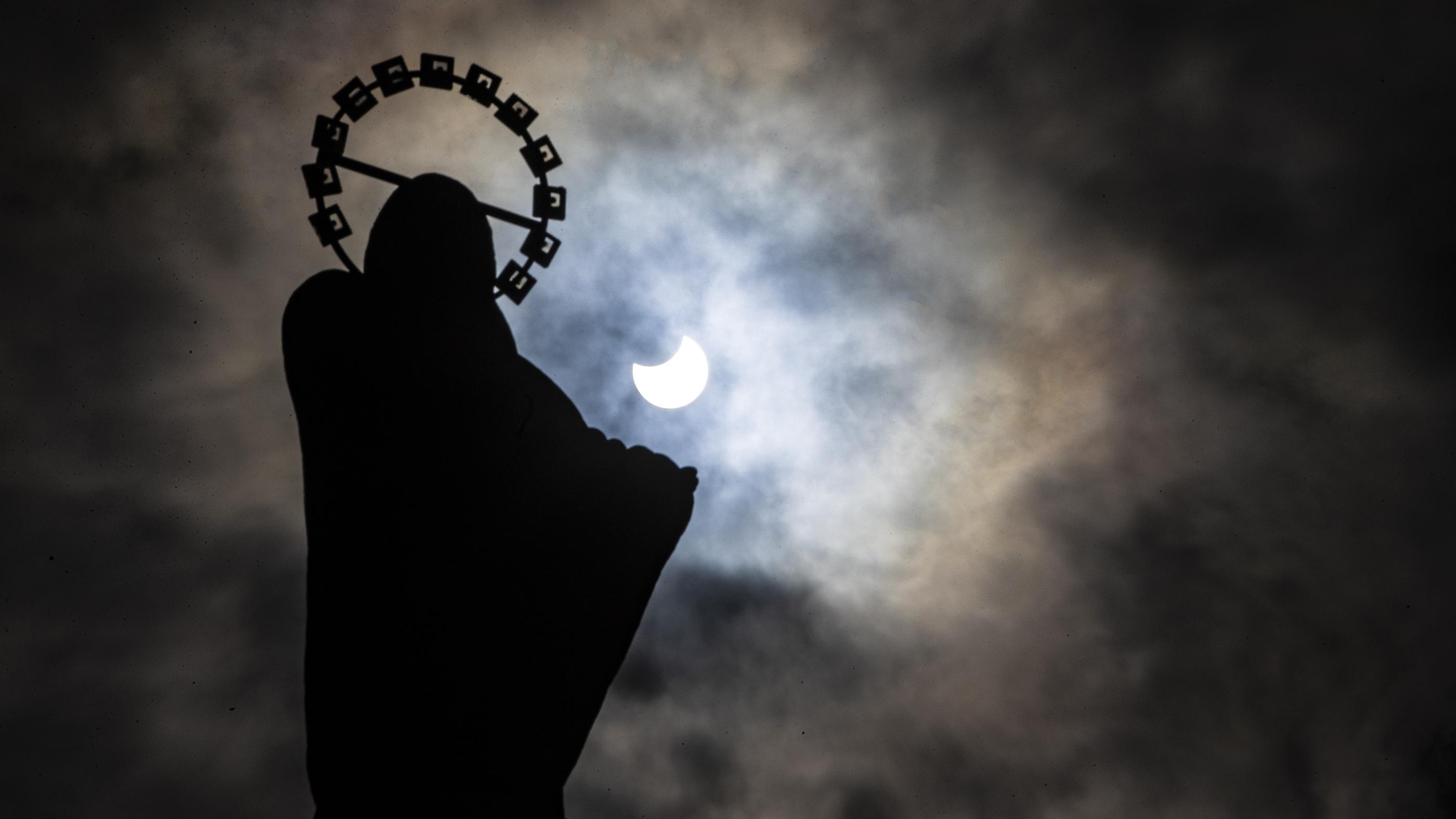 L'éclipse solaire partielle est suspendue derrière une statue de Notre-Dame, l'étoile de la mer sur le mur de Bull à Dublin, le 10 juin 2021. Les observateurs du Royaume-Uni et d'Irlande ont vu un croissant de soleil au lieu du «cercle de feu» formé par l'anneau éclipse.