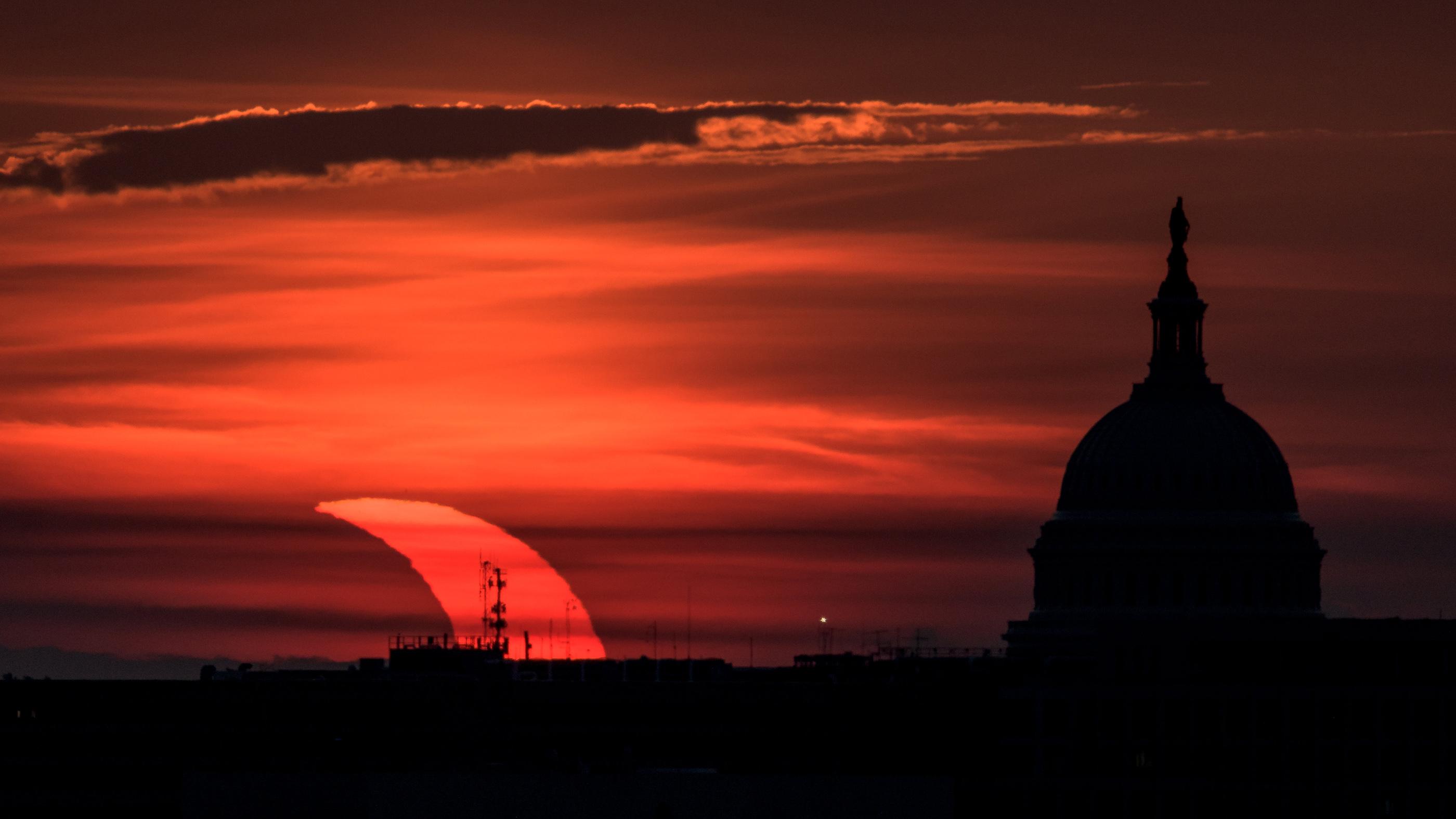 Une éclipse solaire partielle est observée alors que le soleil se lève derrière le Capitole des États-Unis, le jeudi 10 juin 2021, vu d'Arlington, en Virginie.
