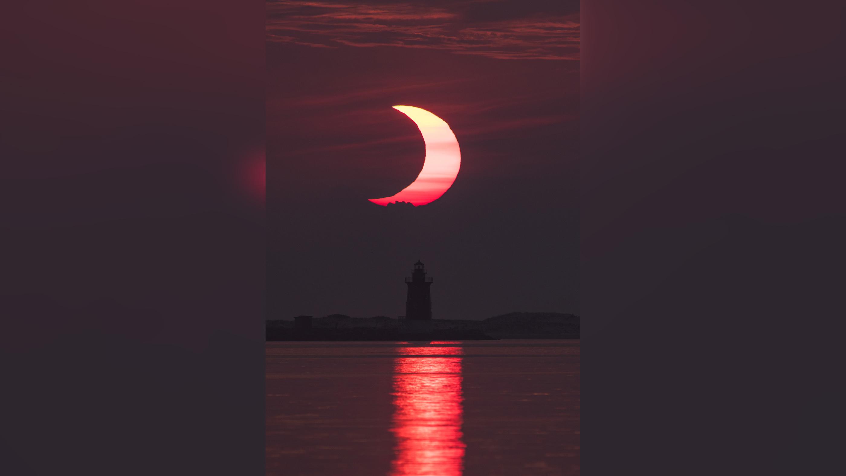 Une éclipse solaire partielle est observée alors que le soleil se lève derrière le phare Delaware Breakwater, le jeudi 10 juin 2021, à Lewes Beach dans le Delaware.