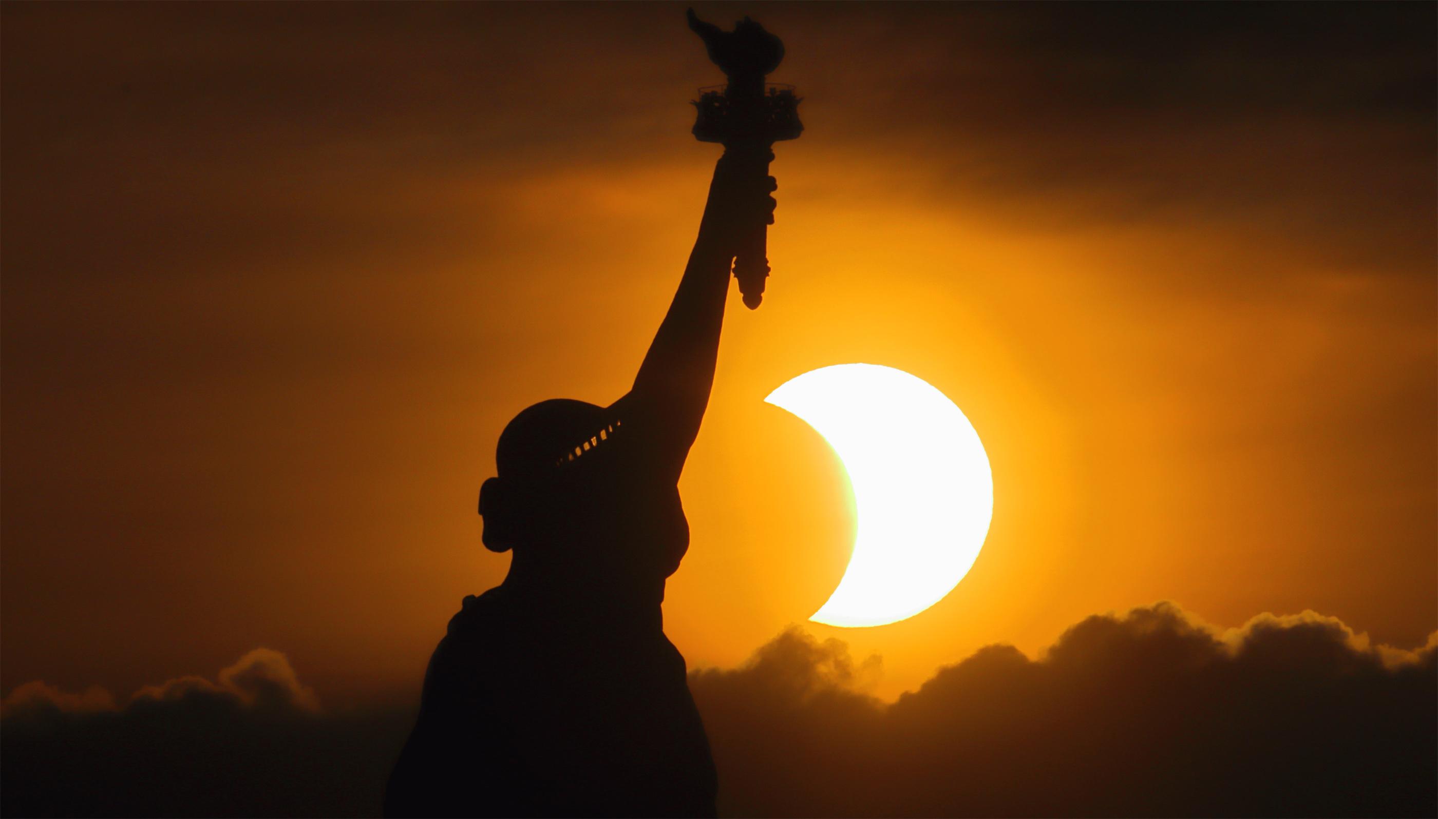 Le soleil se lève à côté de la Statue de la Liberté lors de l'éclipse solaire partielle du 10 juin 2021 à New York.  Une partie des États-Unis a vu le lever du soleil partiellement éclipsé, tandis que d'autres parties de l'hémisphère nord ont été traitées par le «cercle de feu