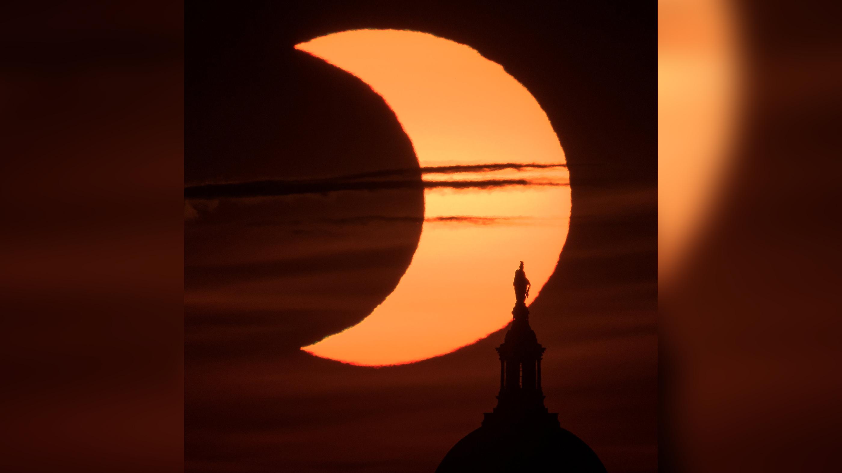 Une éclipse solaire partielle est observée alors que le soleil se lève derrière la Statue de la Liberté au sommet du Capitole des États-Unis, le jeudi 10 juin 2021, vue d'Arlington, en Virginie.