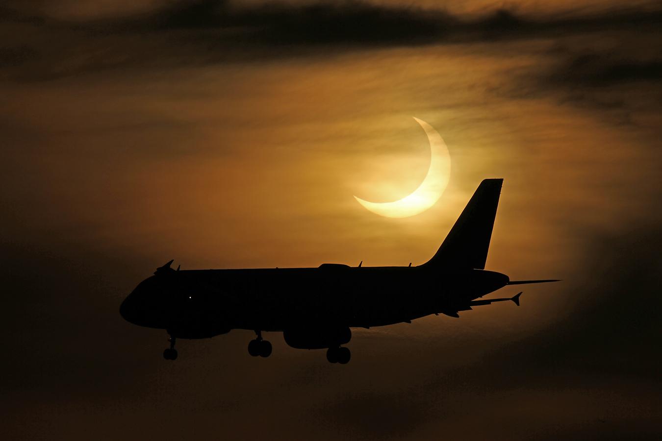 Un avion vole devant le soleil partiellement éclipsé sur cette superbe photo des photographes Imelda Joson et Edwin Aguirre au Black Falcon Cruise Ship Terminal à Boston le 10 juin 2021.