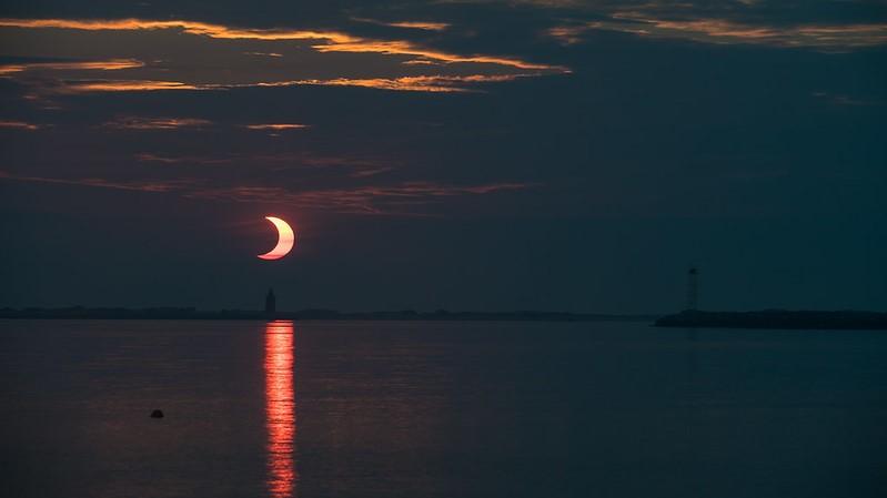 Une vue du soleil partiellement éclipsé se levant au-dessus du phare Delaware Breakwater le 10 juin 2021, par Aubrey Gemignani.