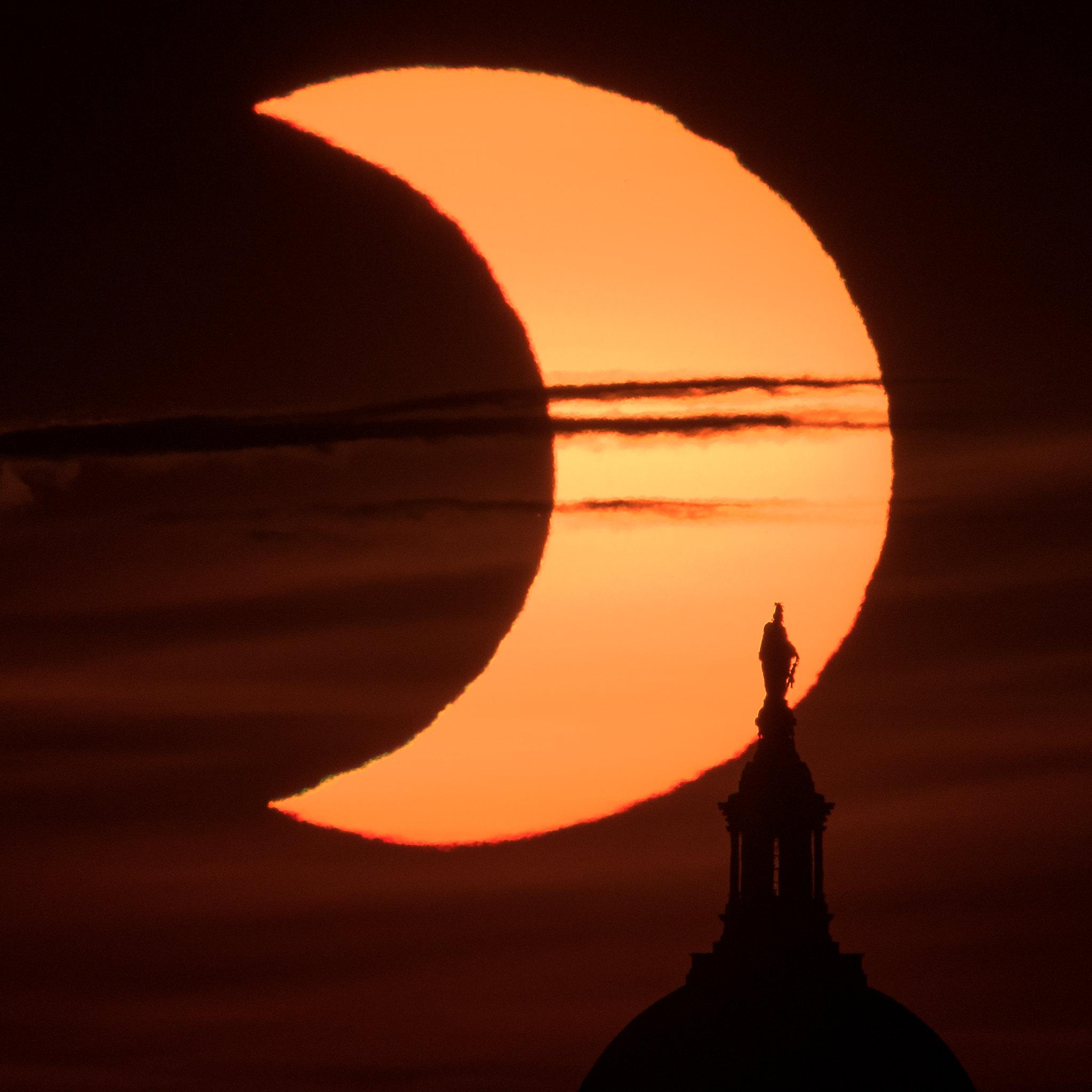 Une éclipse solaire partielle est vue alors que le soleil se lève derrière la Statue de la Liberté au sommet du Capitole des États-Unis le 10 juin 2021, vue d'Arlington, en Virginie, par le photographe de la NASA Bill Ingalls.