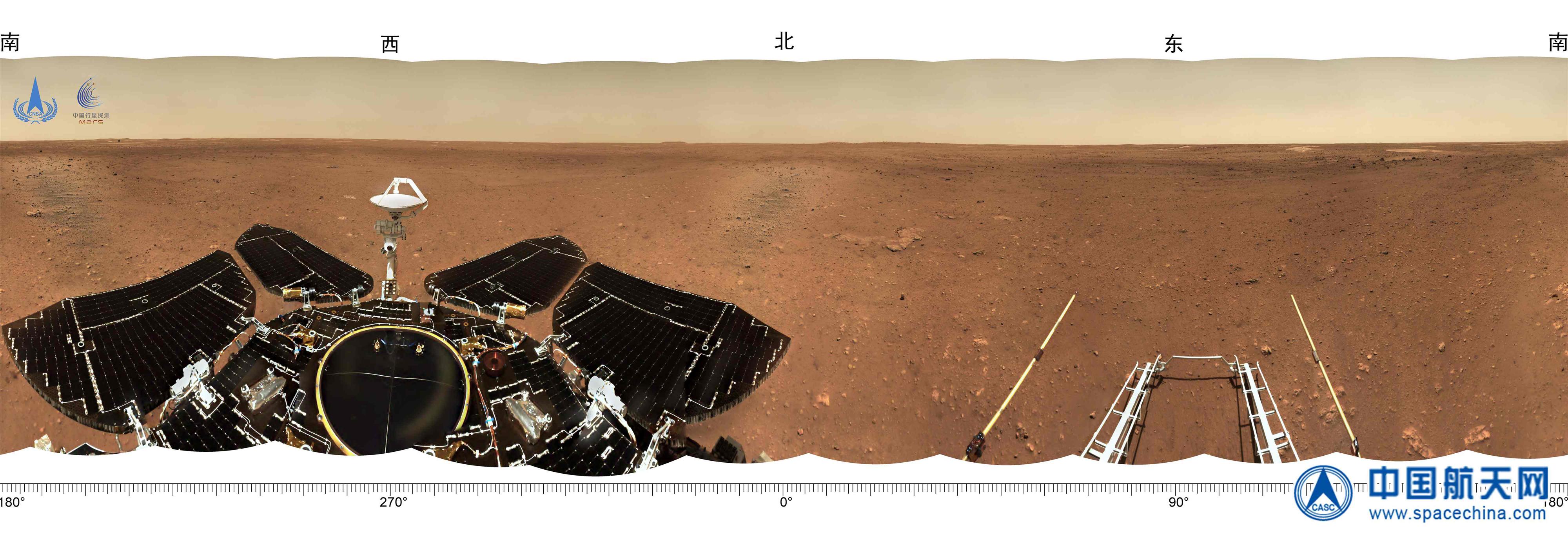 Ce panorama du rover chinois Zhurong montre la vaste plaine plate de son site d'atterrissage Utopia Planitia.  Les panneaux solaires et le pont du rover sont visibles à gauche et les rampes de roues de son atterrisseur sont visibles à droite.