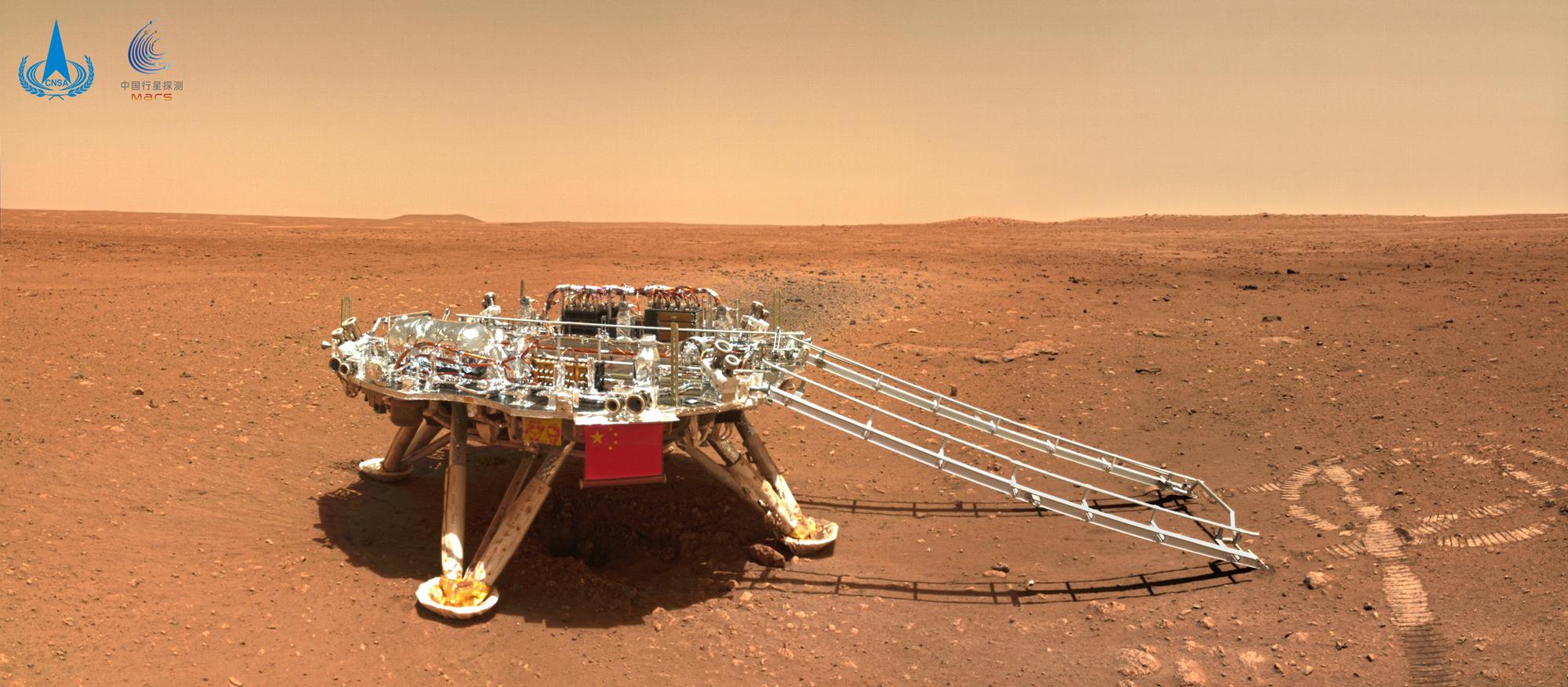 Cette photo du rover chinois Zhurong montre une vue latérale de son atterrisseur Tianwen 1 sur son site d'atterrissage à Utopia Planitia.  Les traces du rover sont visibles à droite. Cette image a été publiée le 11 juin 2021.
