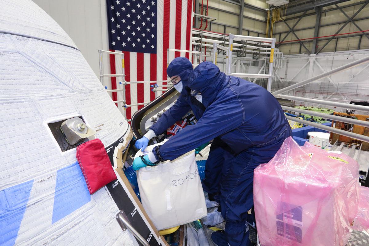Les techniciens de Boeing chargent un paquet de souvenirs à bord de la capsule Orbital Flight Test-2 Starliner en vue de son lancement.
