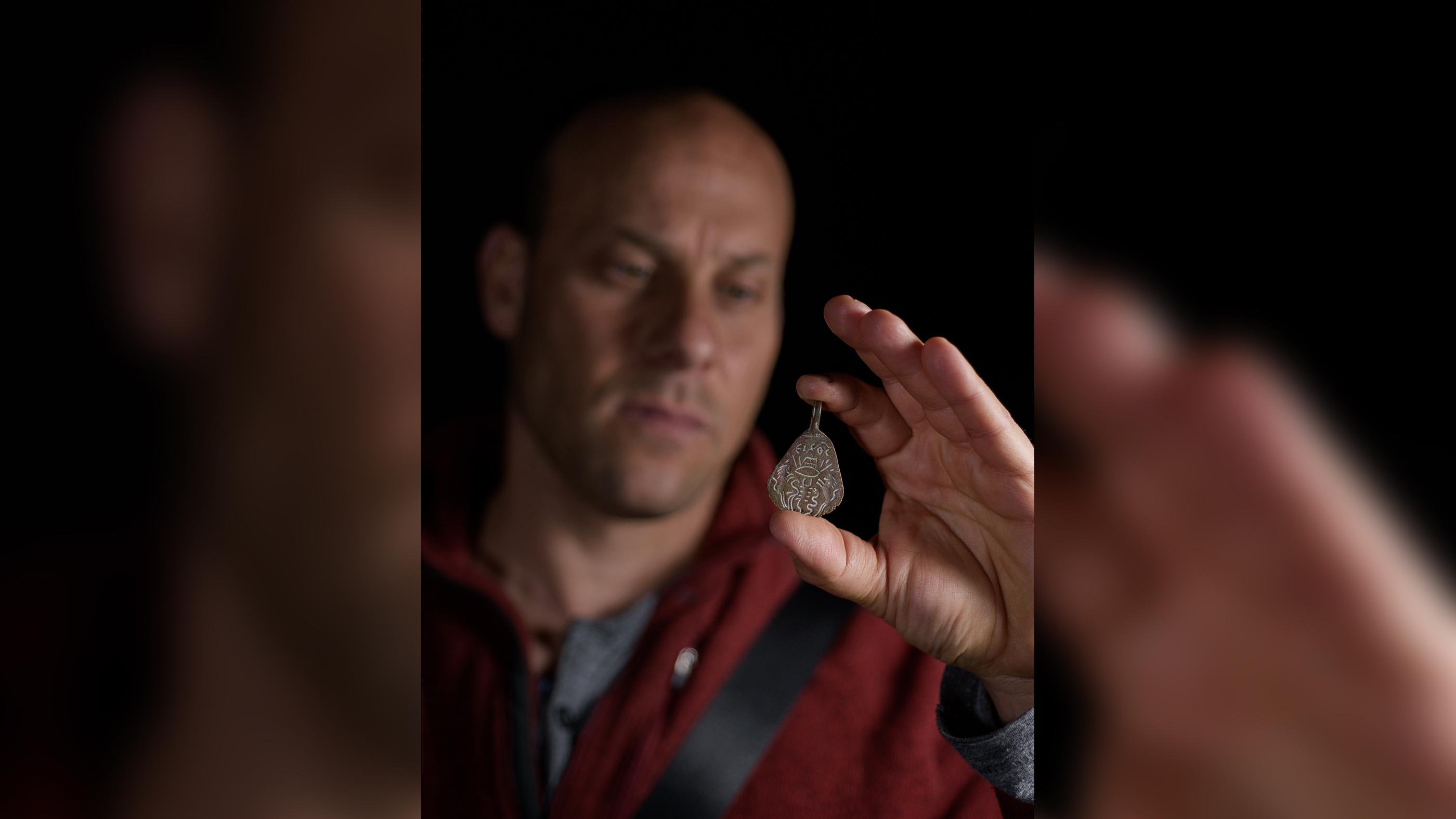 L'archéologue de l'IAA Eitan Klein tenant l'amulette, qui aurait environ 1500 ans et était destinée à repousser les